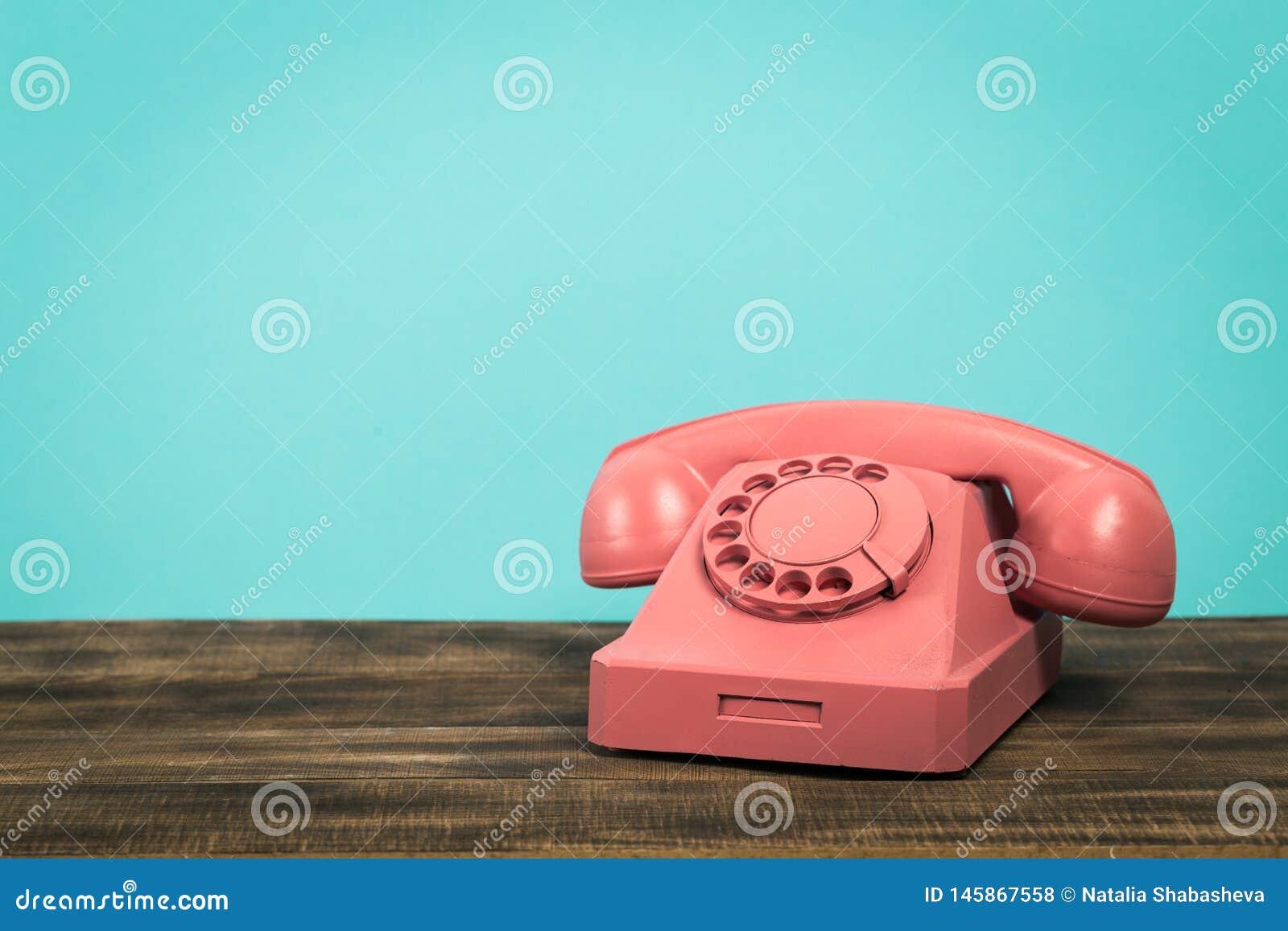 Teléfono rosado retro en la tabla en fondo delantero del verde menta