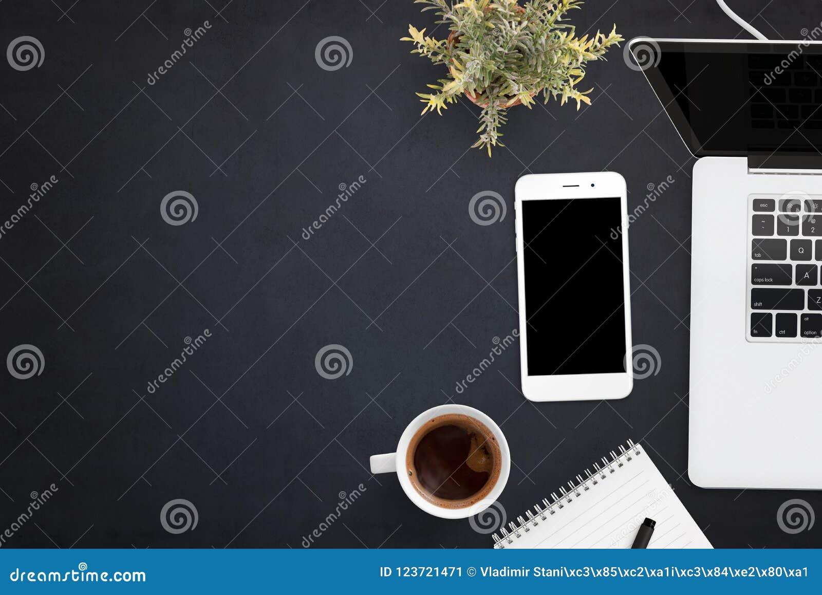 Teléfono y ordenador portátil elegantes en el escritorio de oficina negro con el espacio de la copia en lado izquierdo
