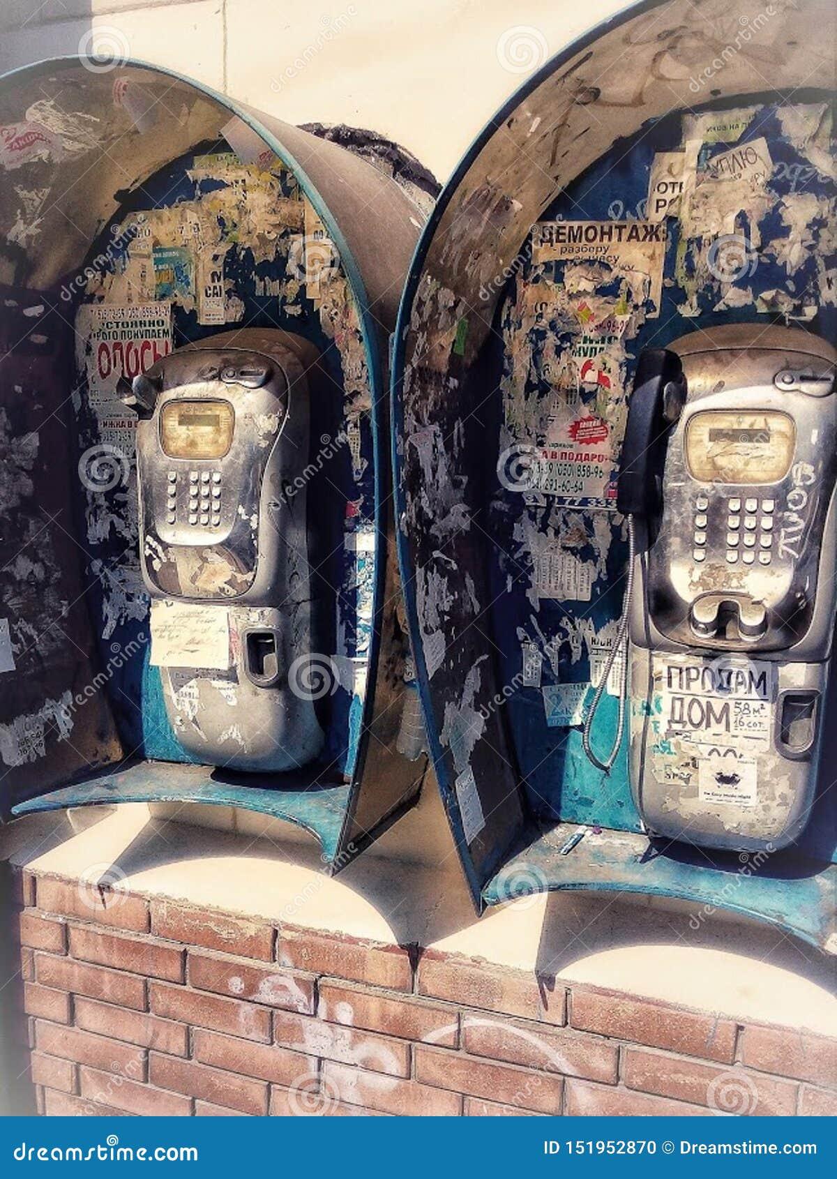 Teléfonos de pago del siglo XX en una calle de la ciudad, anuncios viejos en una pared, teléfonos con los receptores