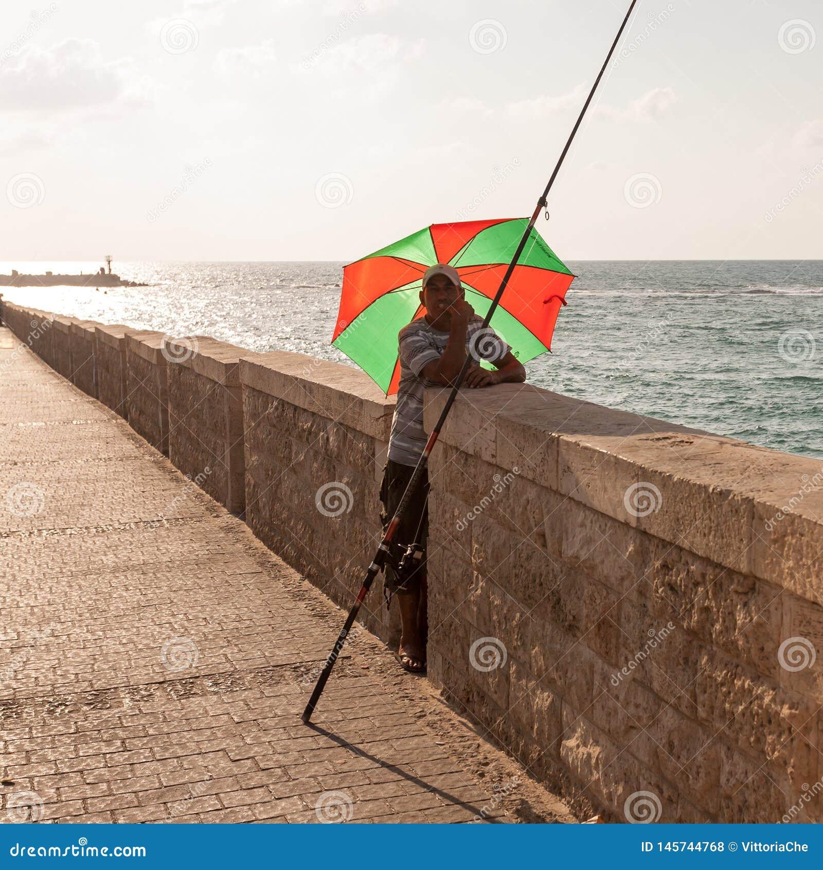 Tel Aviv, Israele - 9 settembre 2011: Pesca adulta dell uomo sotto l ombrello nel telefono Aviv Promenade