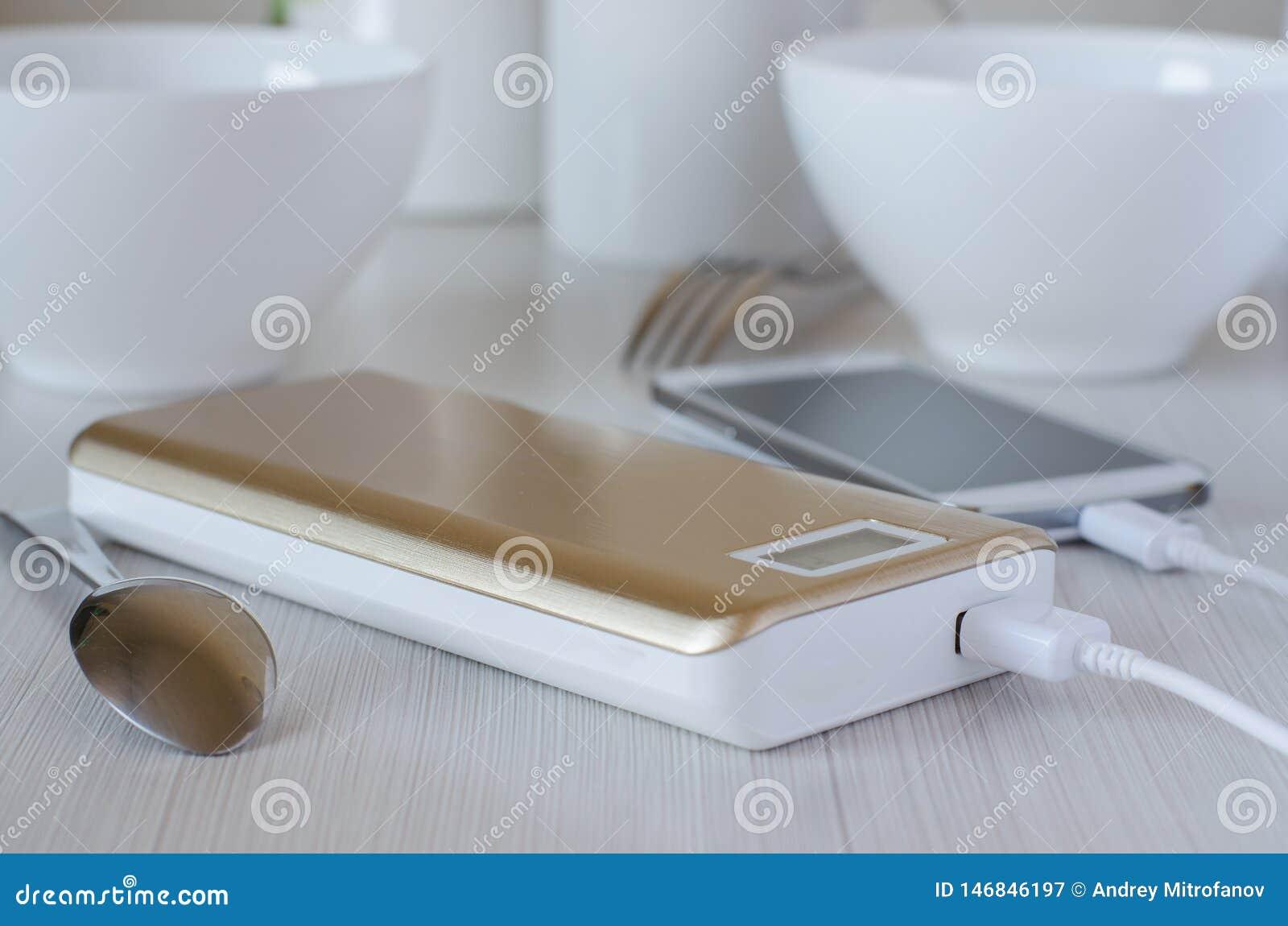 Tel?fono celular de los gastos bancarios del poder en la tabla de cocina
