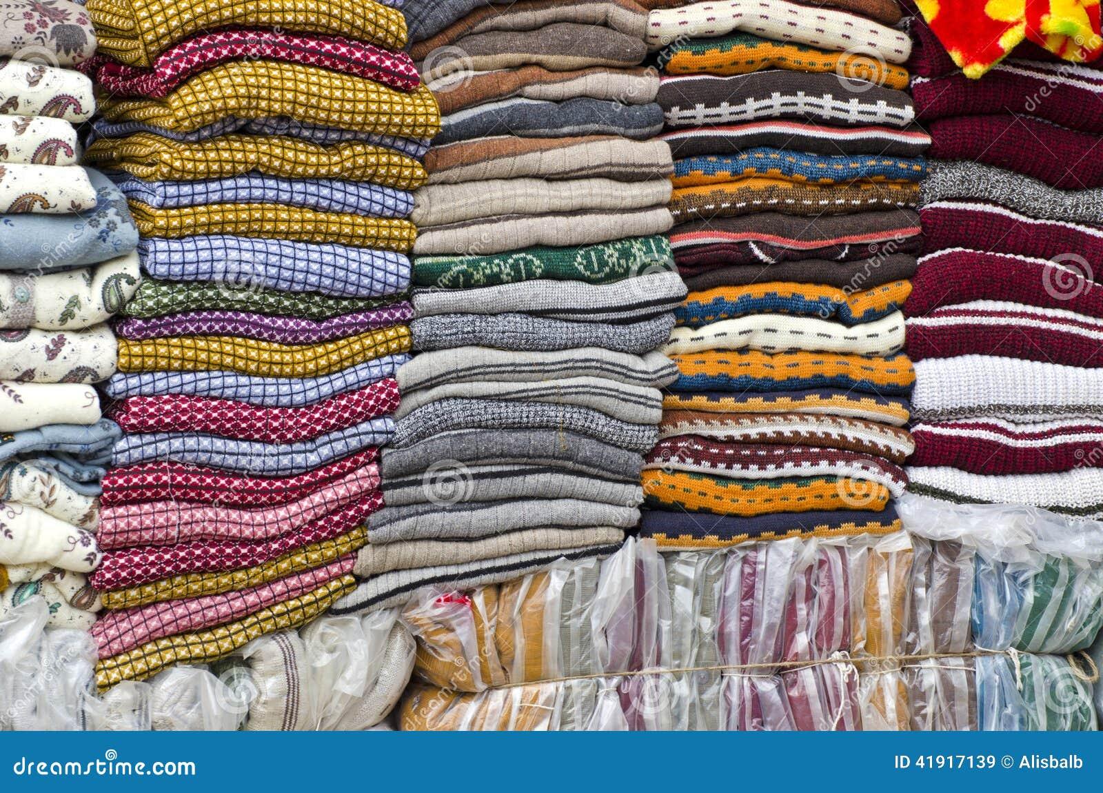 Tela apilada colorida en el mercado grande, la India