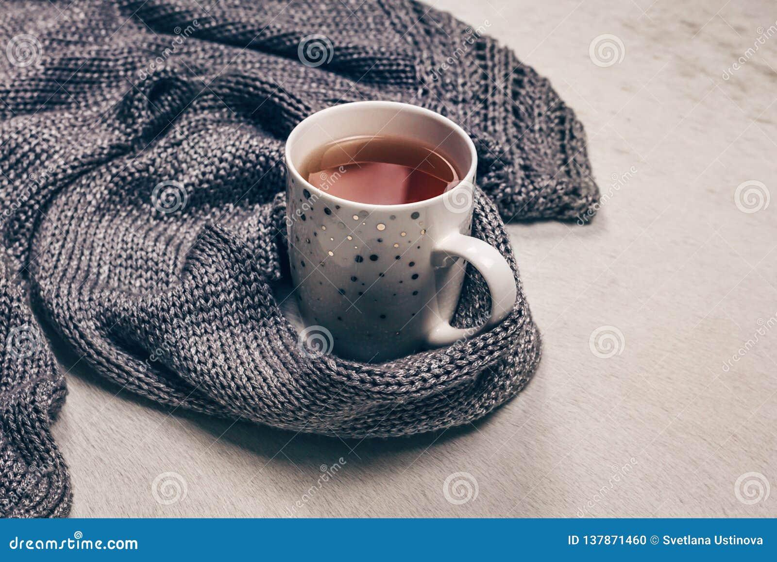 Tela feita malha cinzenta prateada ao longo de um copo do chá no fundo branco leitoso da pele