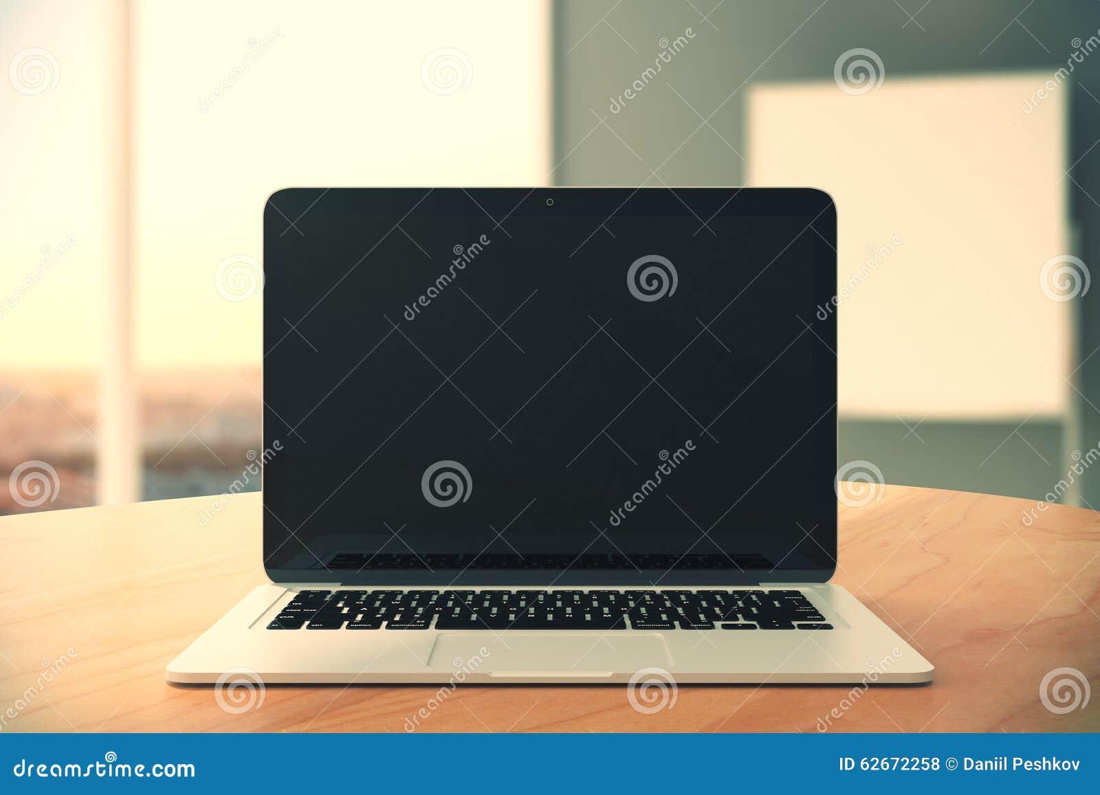 Tela preta vazia do portátil na tabela de madeira no backgr vazio do escritório