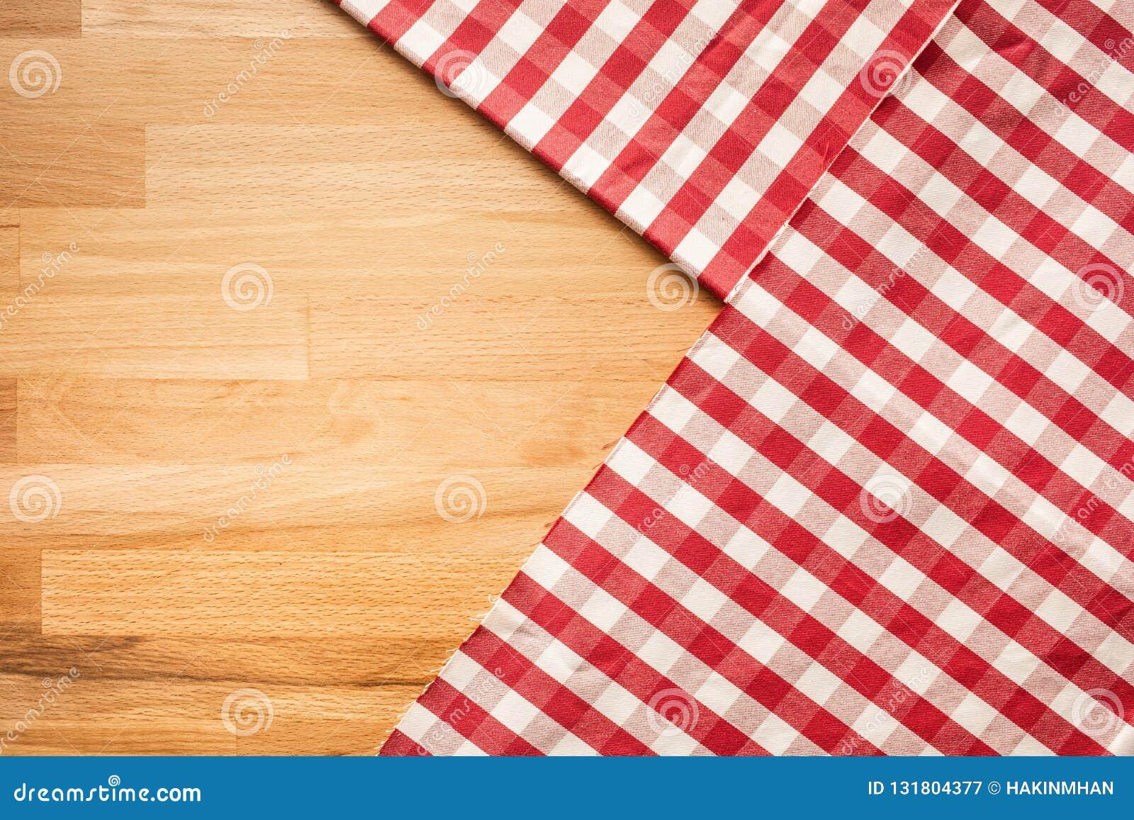 Tela quadriculado vermelha no fundo de madeira da tabela Para a decoração