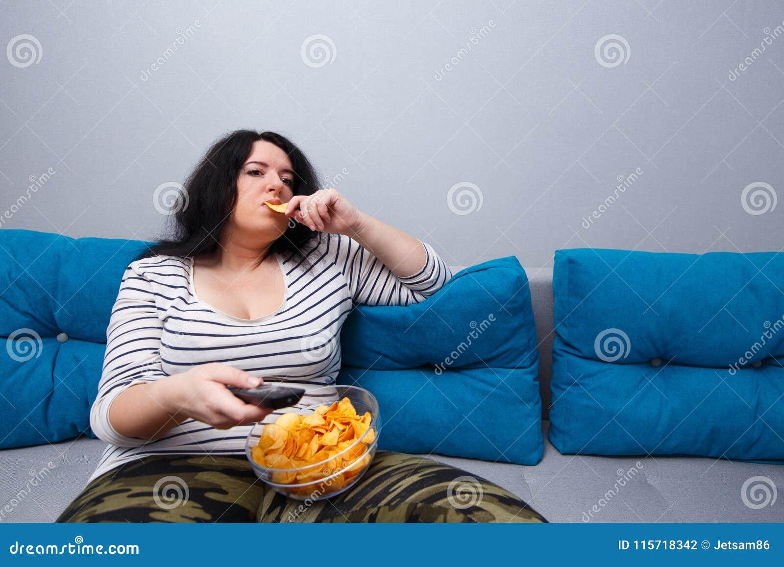 Tele-leń kobiety z nadwagą obsiadanie na kanapie, łasowanie szczerbi się