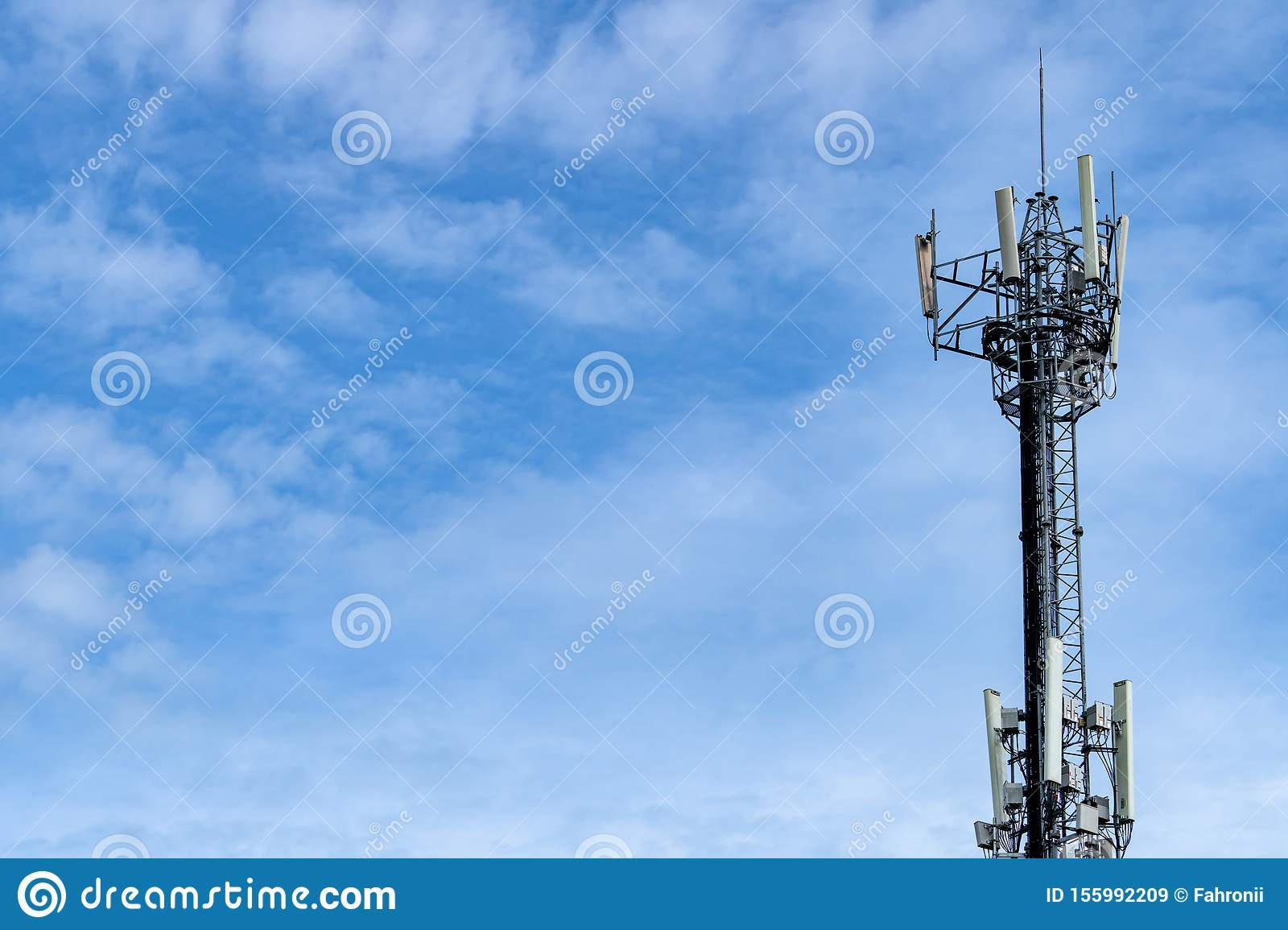Telecommunication tower with blue sky and white clouds background. Antenna on blue sky. Radio and satellite pole. Communication