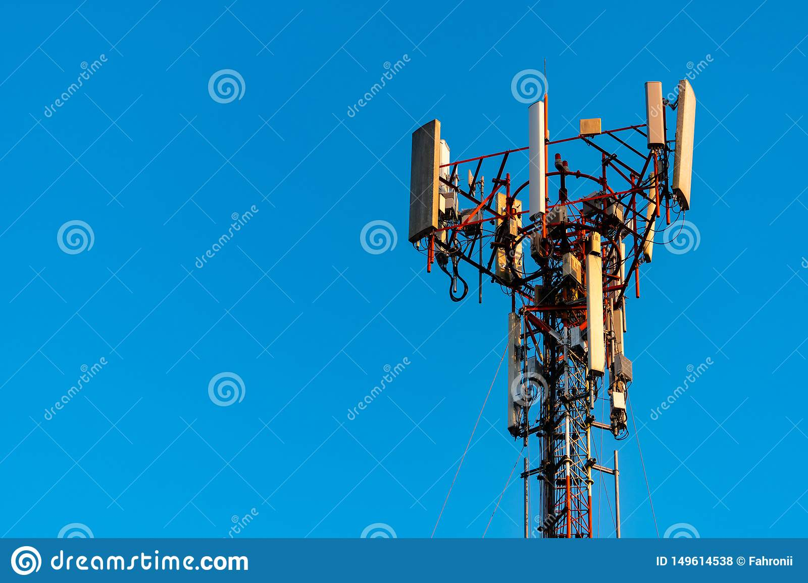 Telecommunication tower with clear blue sky background. Antenna on blue sky background. Radio and satellite pole. Communication