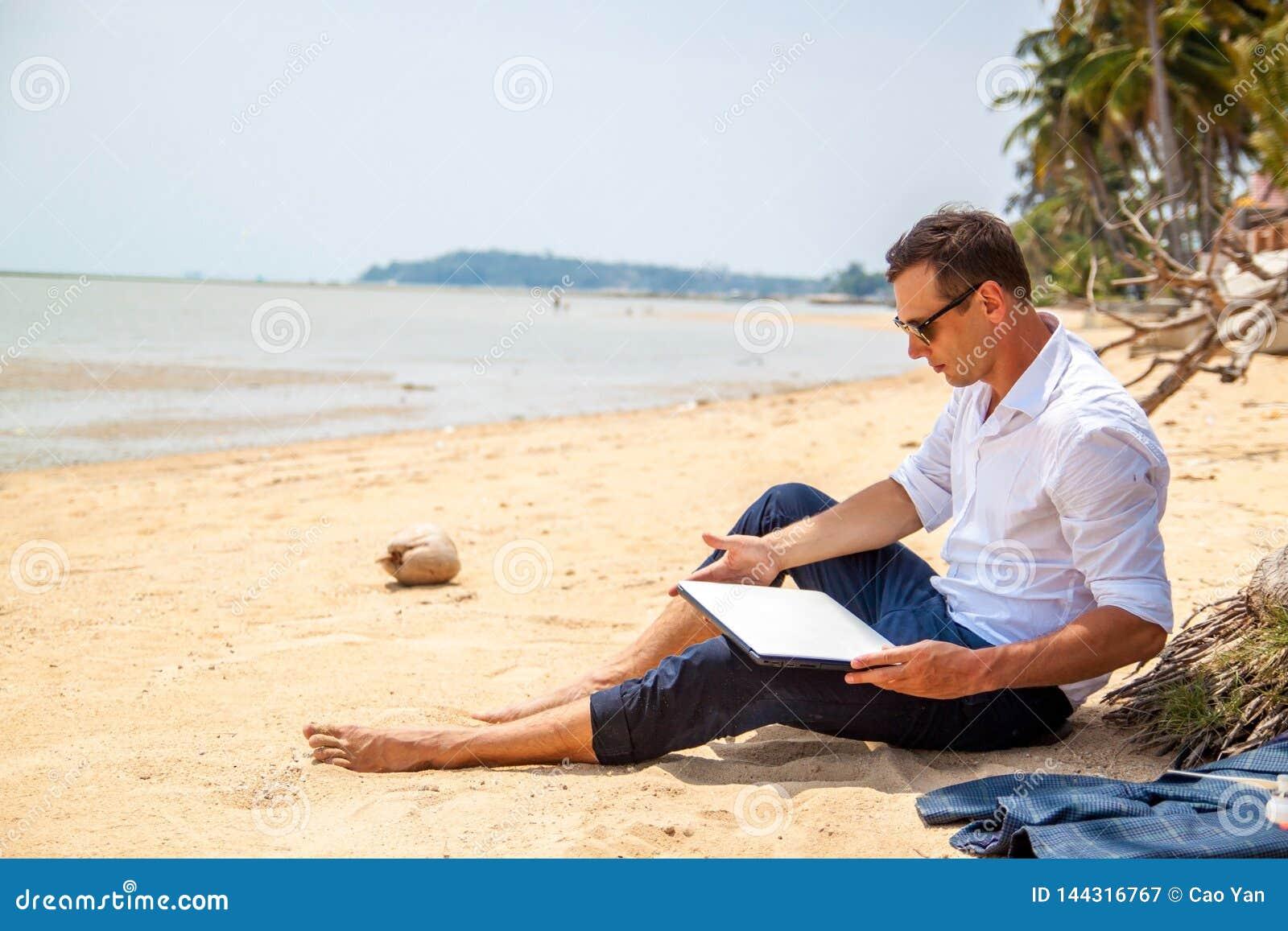 Telecommuting aff?rsmannen som kopplar av p? stranden med b?rbara datorn och, g?mma i handflatan, freelancerarbetsplatsen, dr?m-