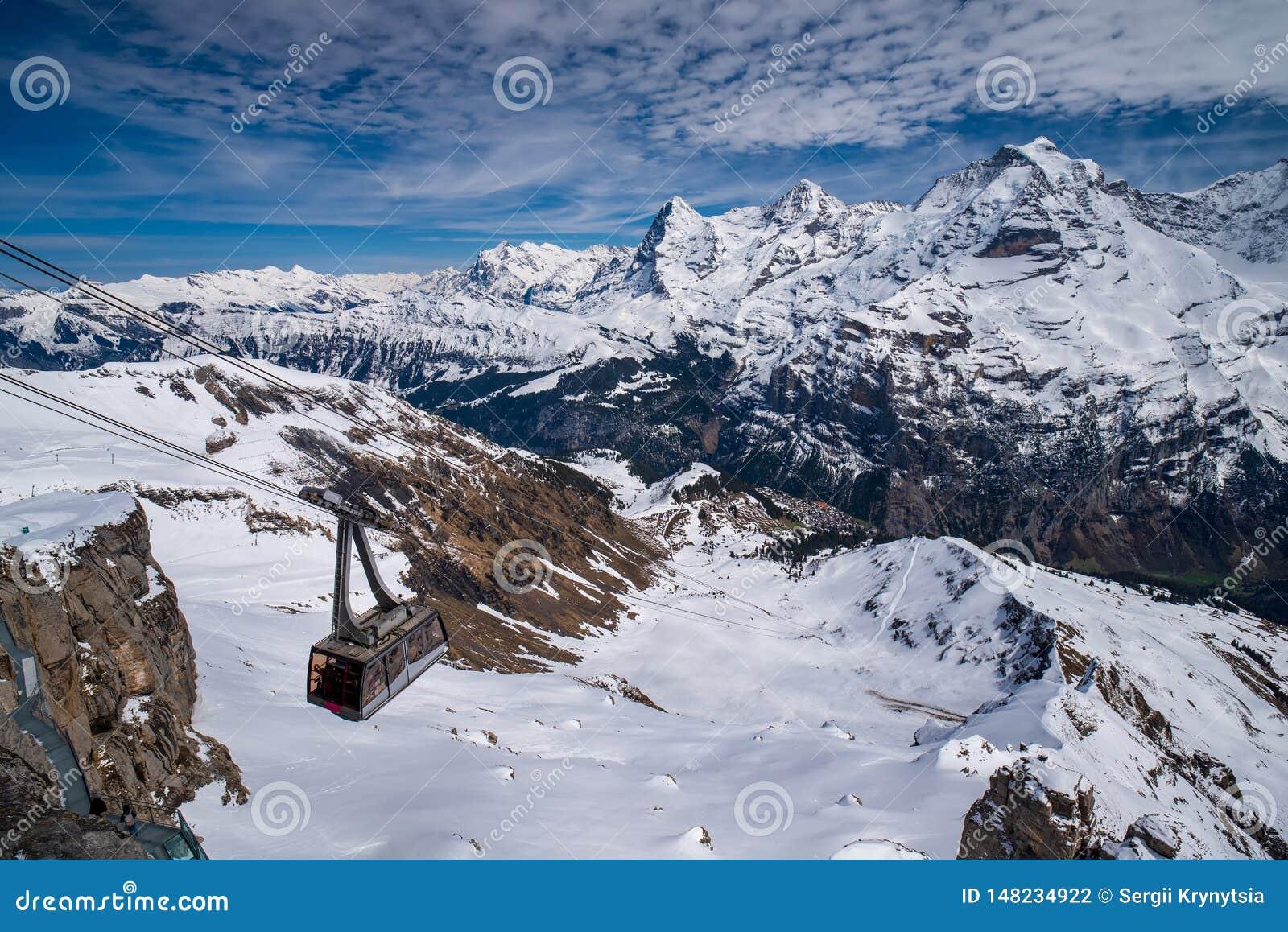 Telef?rico contra a vista panor?mica excitante de picos famosos Eiger, Monch e Jungfrau em cumes su??os, Su??a