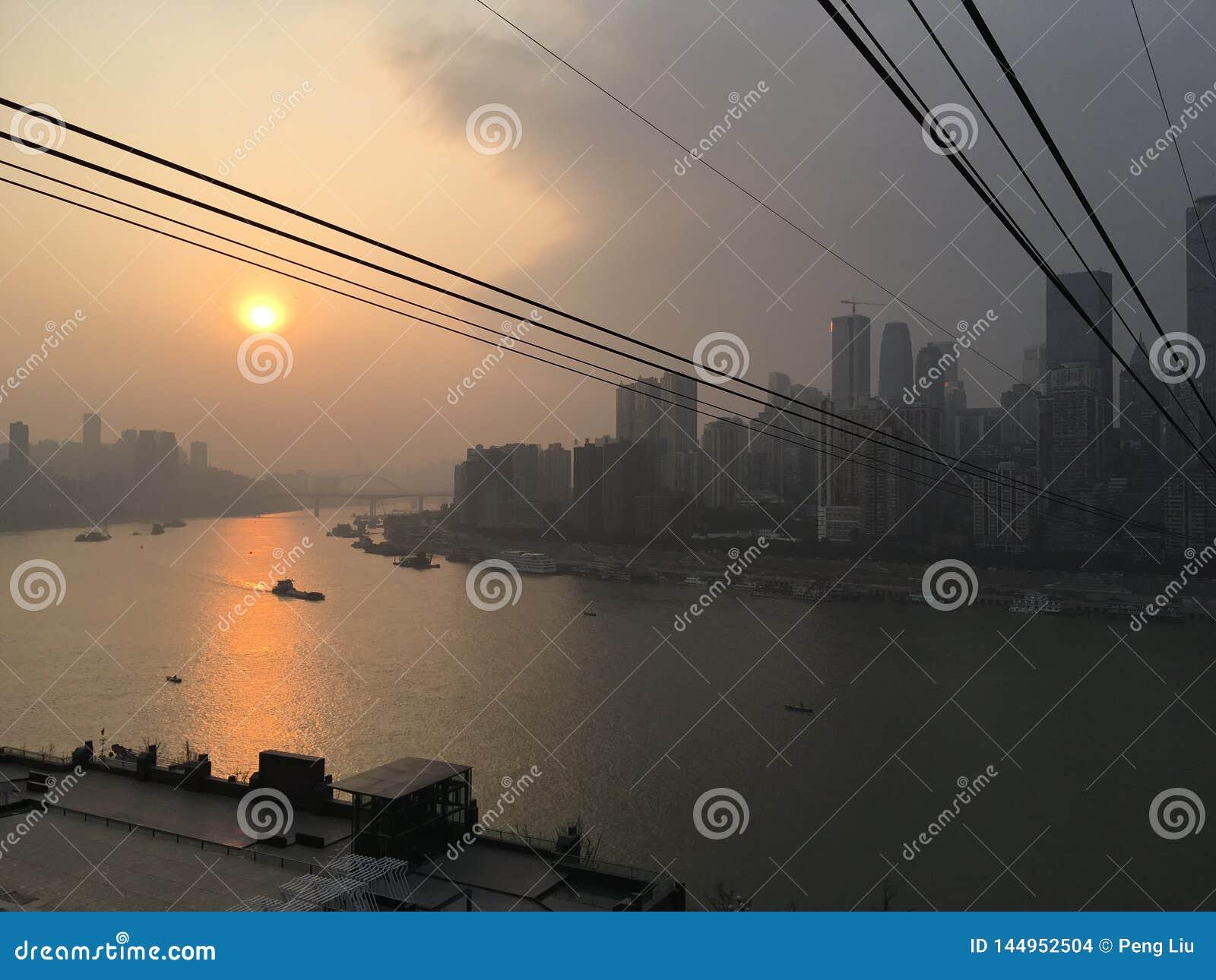 Teleférico do navio do rio do por do sol da cidade