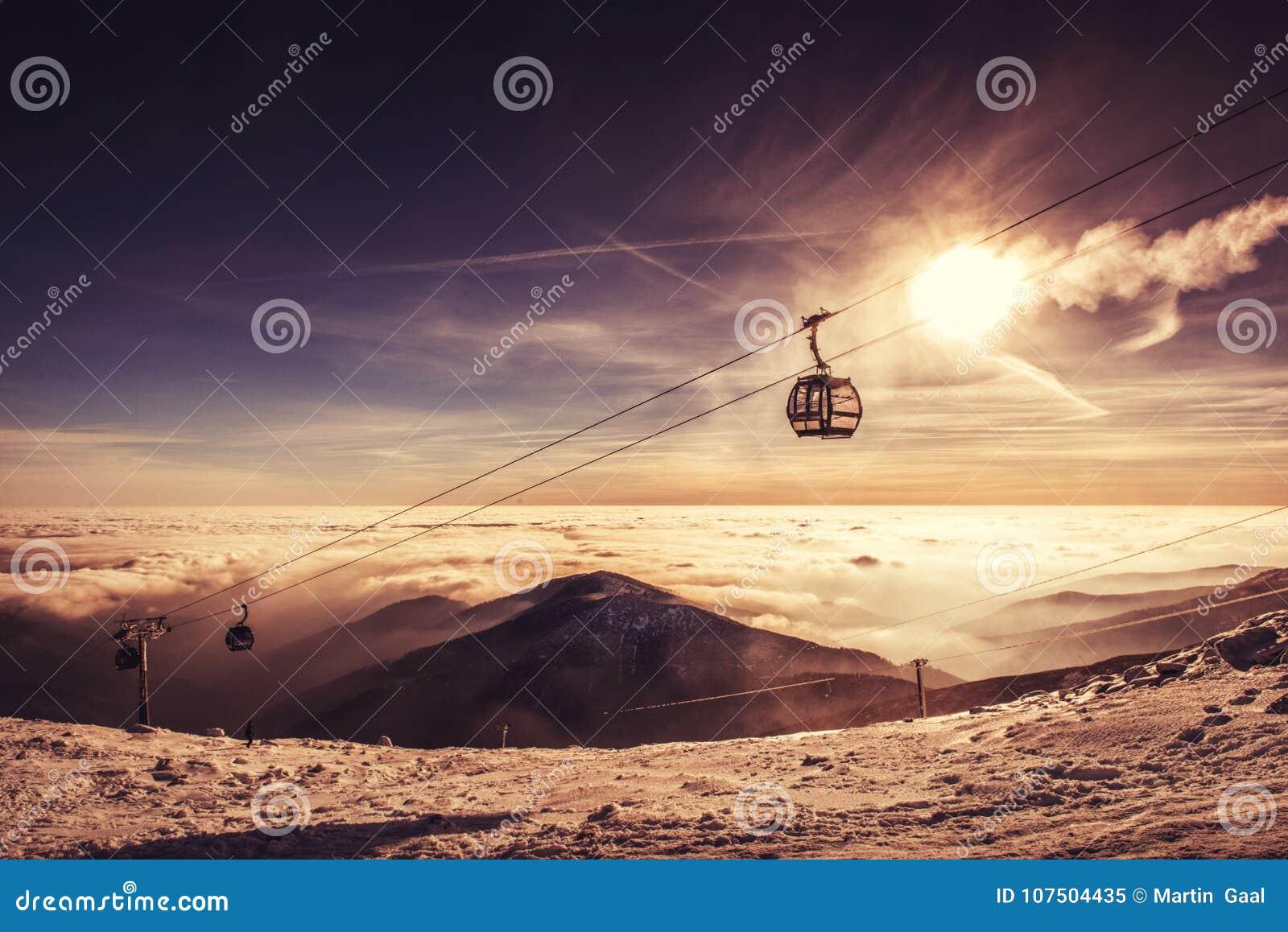 Teleférico na montanha do inverno, cenário inverso no nascer do sol