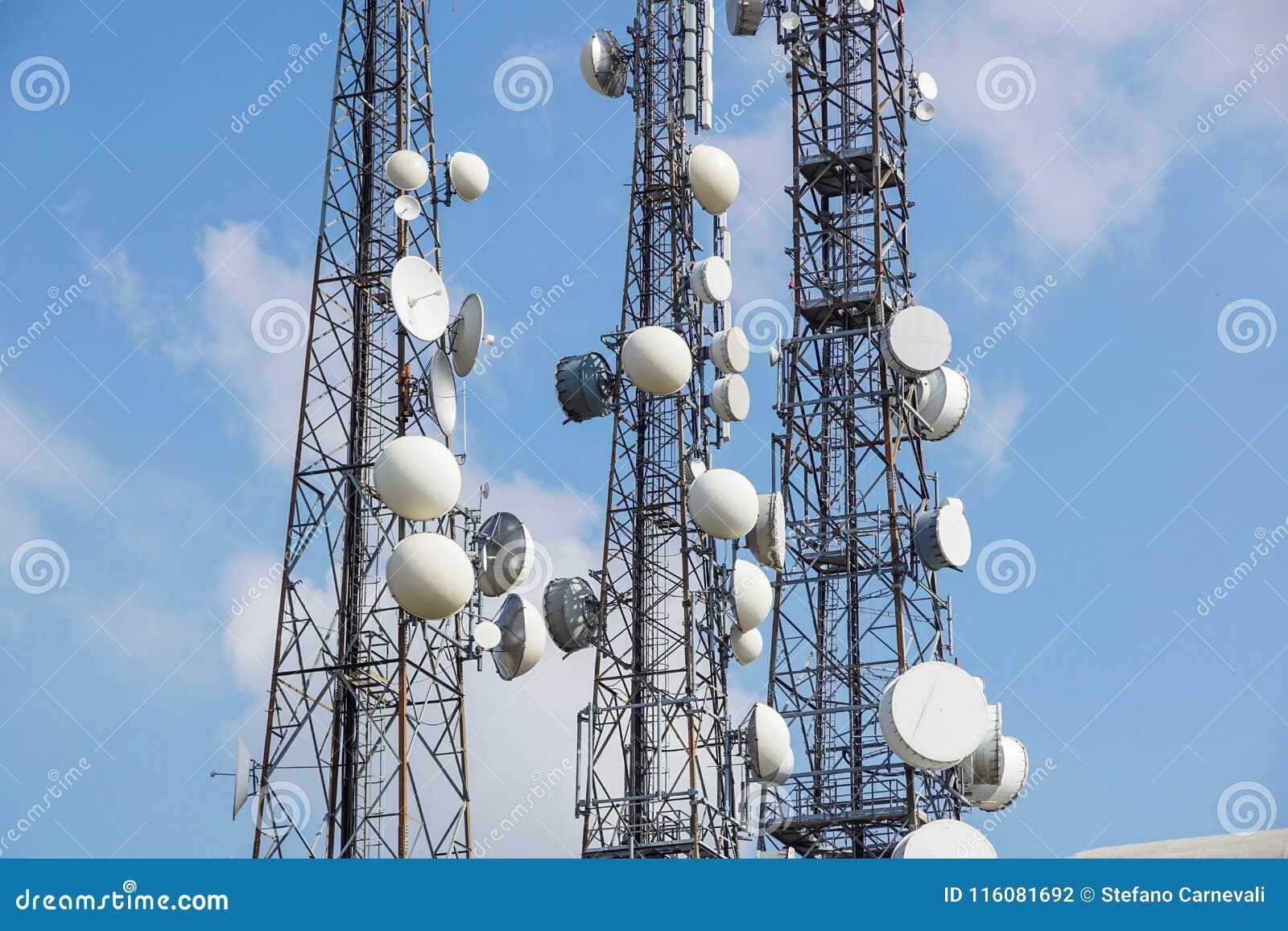 Telefon komórkowy anteny komunikacyjny wierza z anteną satelitarną na niebieskiego nieba tle, telekomunikaci wierza