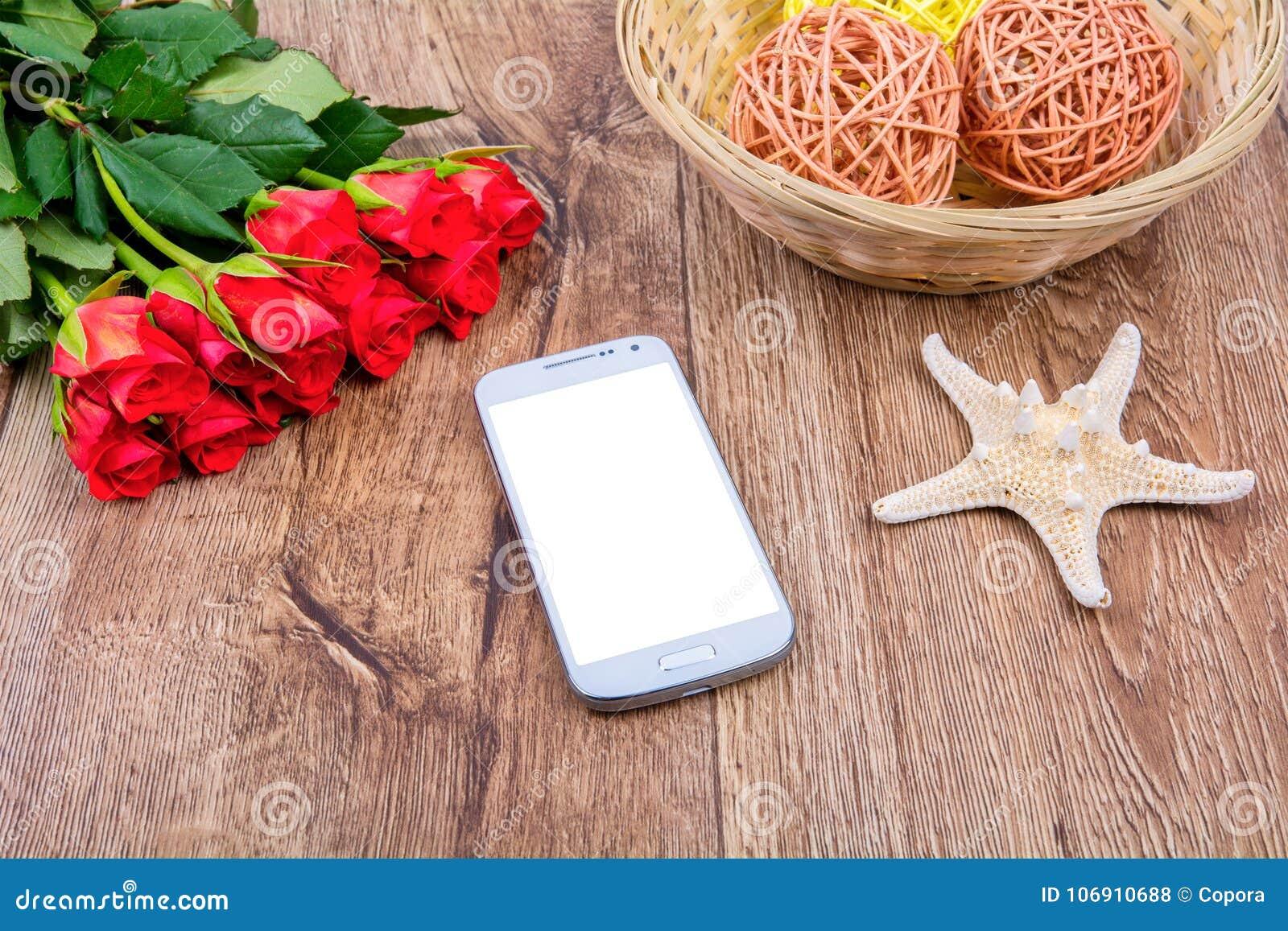Telefon komórkowy, rozgwiazda i róże na drewnianym stole,