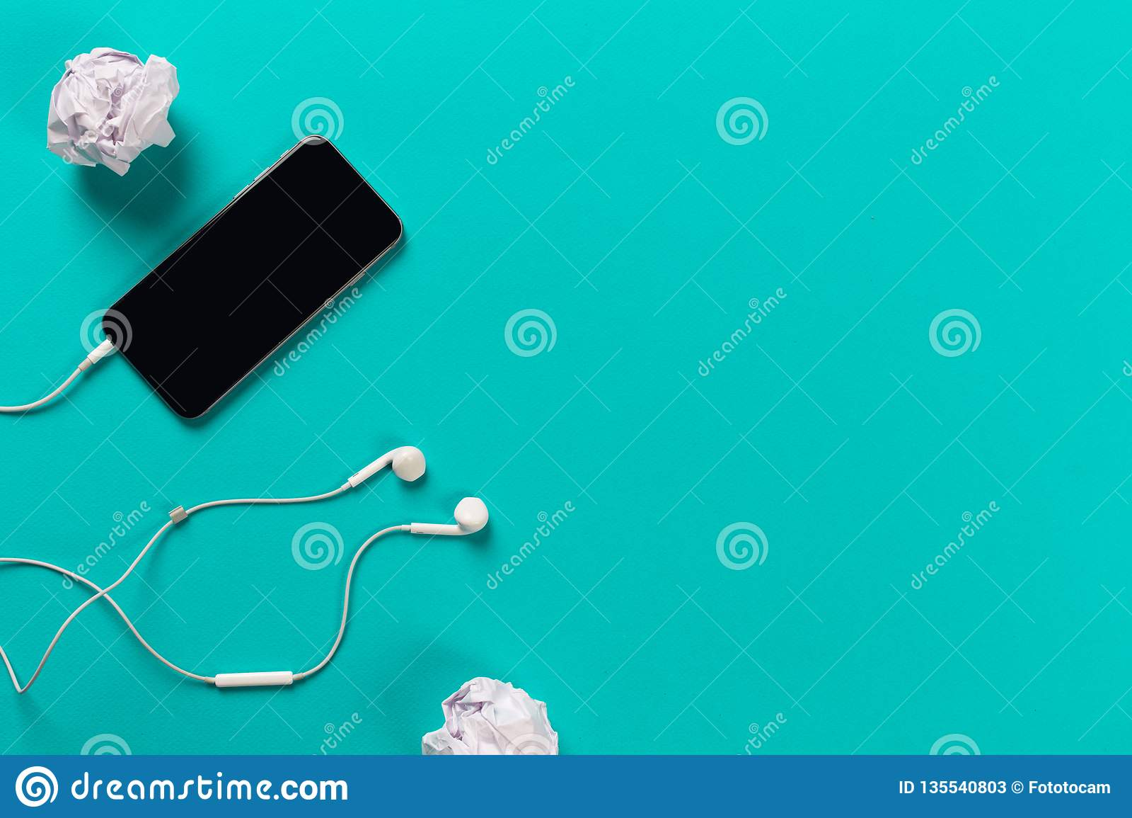 Telefon komórkowy z białymi słuchawkami na colour backgroung z staczającym się papierem, odgórny widok