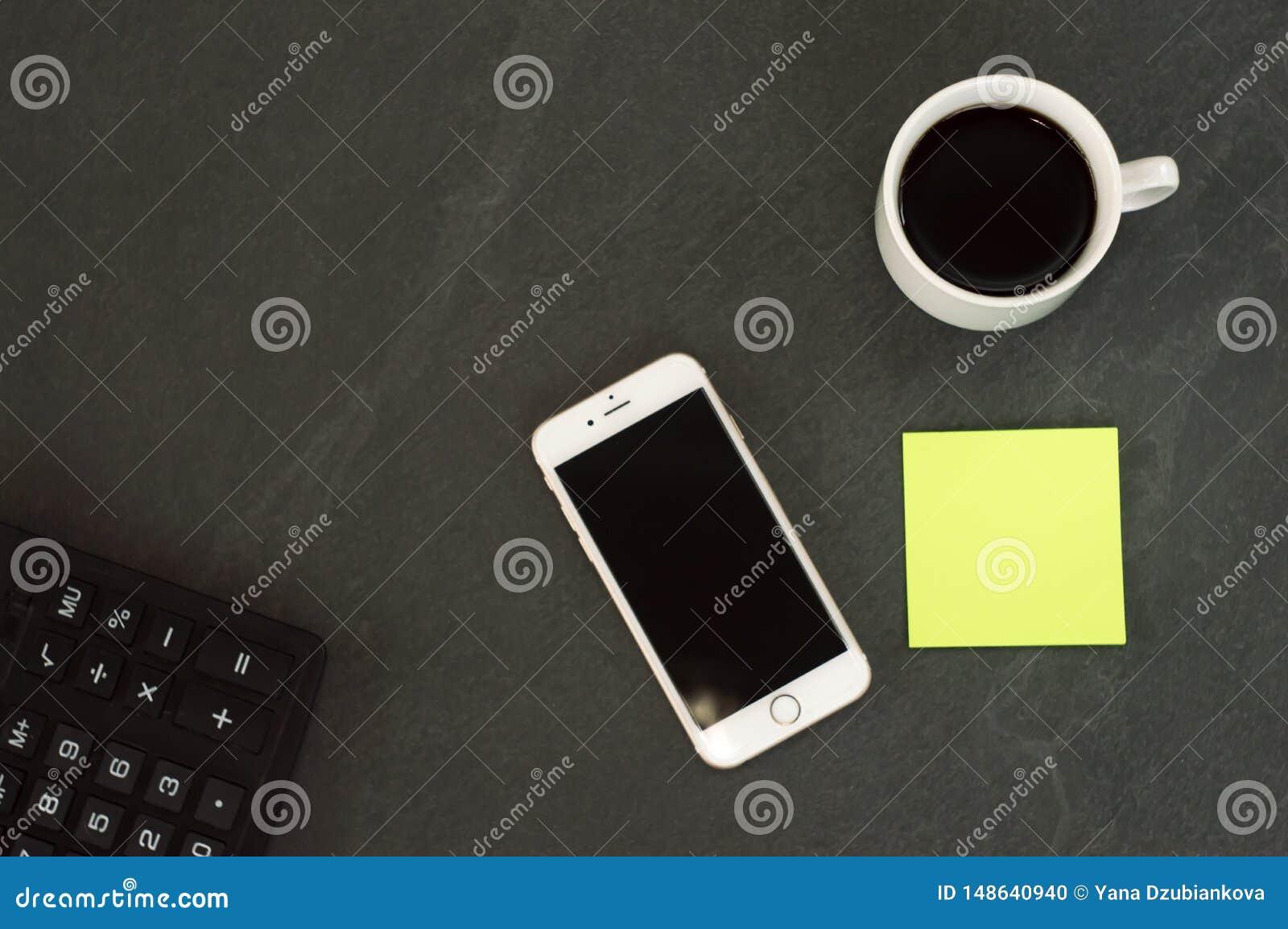 Telefone branco com uma x?cara de caf?, uma pena vermelha e uma mentira da calculadora em uma tabela de madeira branca