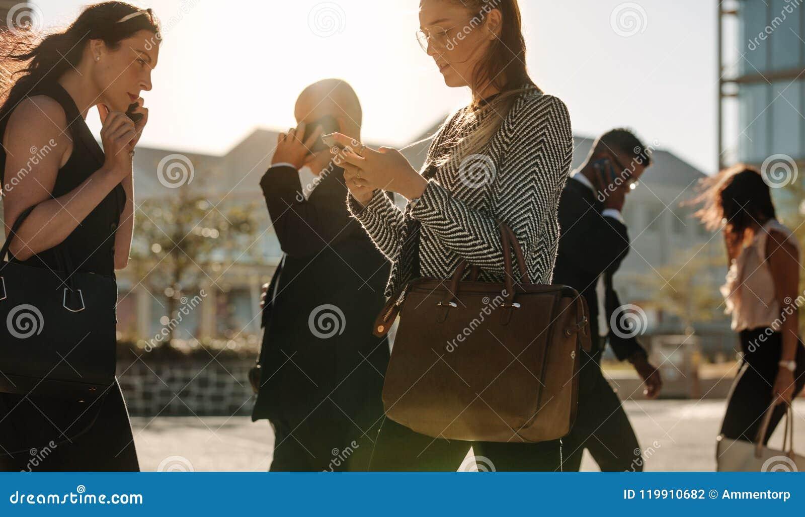 Telefone celular de utilização ocupado dos povos ao andar na rua ao escritório