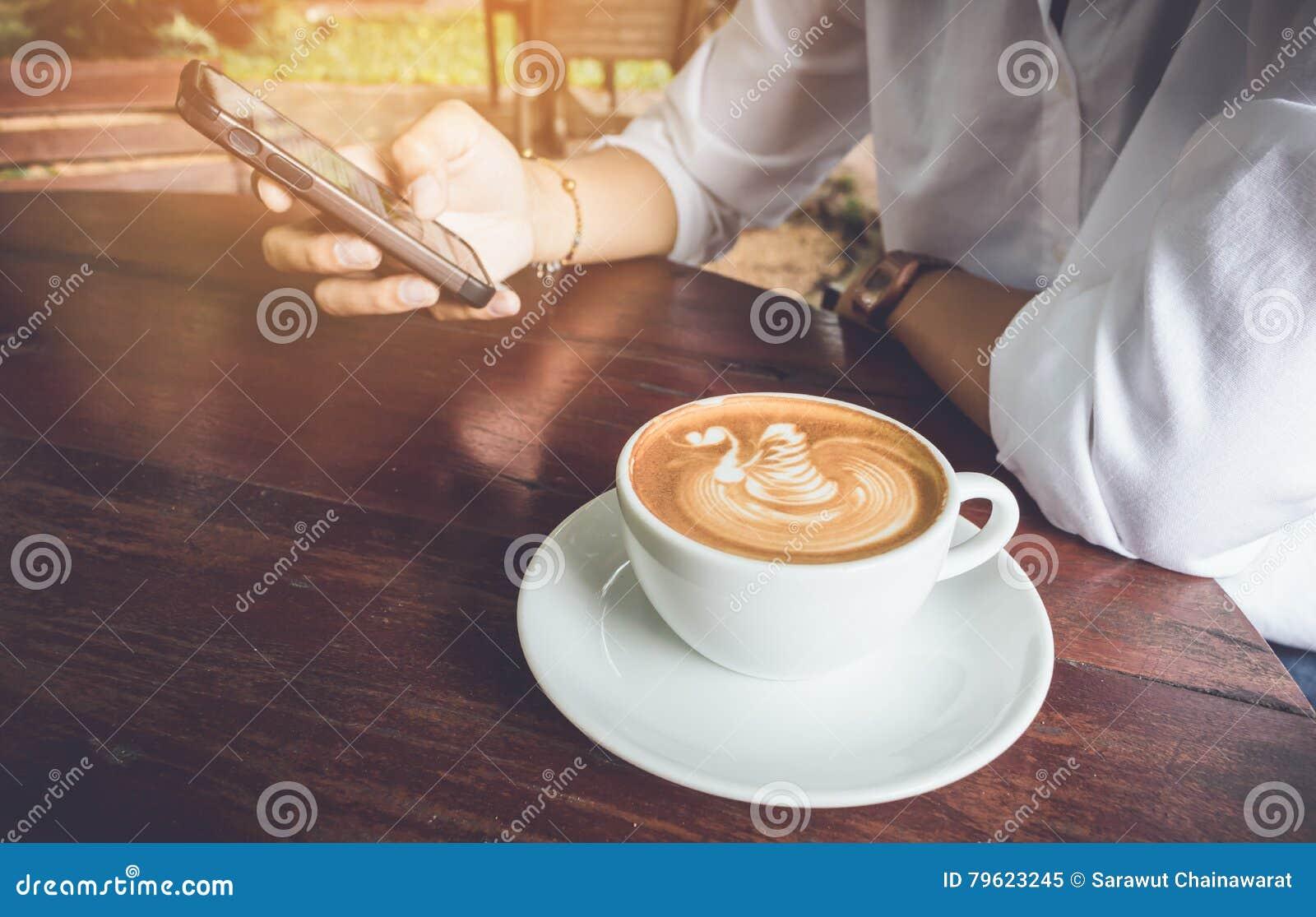 Telefone celular do uso da mulher com tom do vintage do copo de café