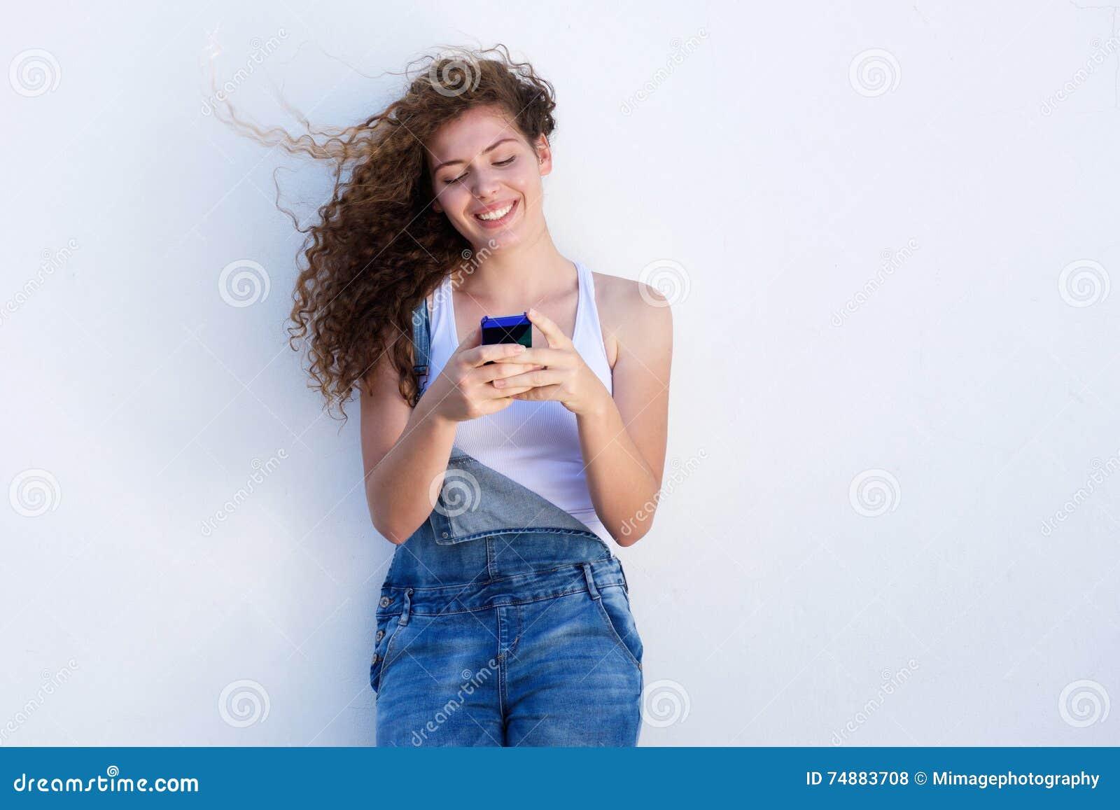 Telefone celular guardando adolescente feliz e sorriso com sopro do cabelo