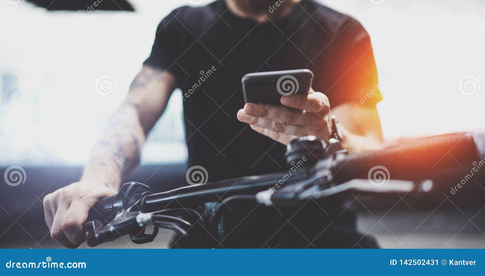 Telefone celular muscular Tattooed da terra arrendada do homem nas mãos e em usar o app do mapa para preparar a rota da estrada d