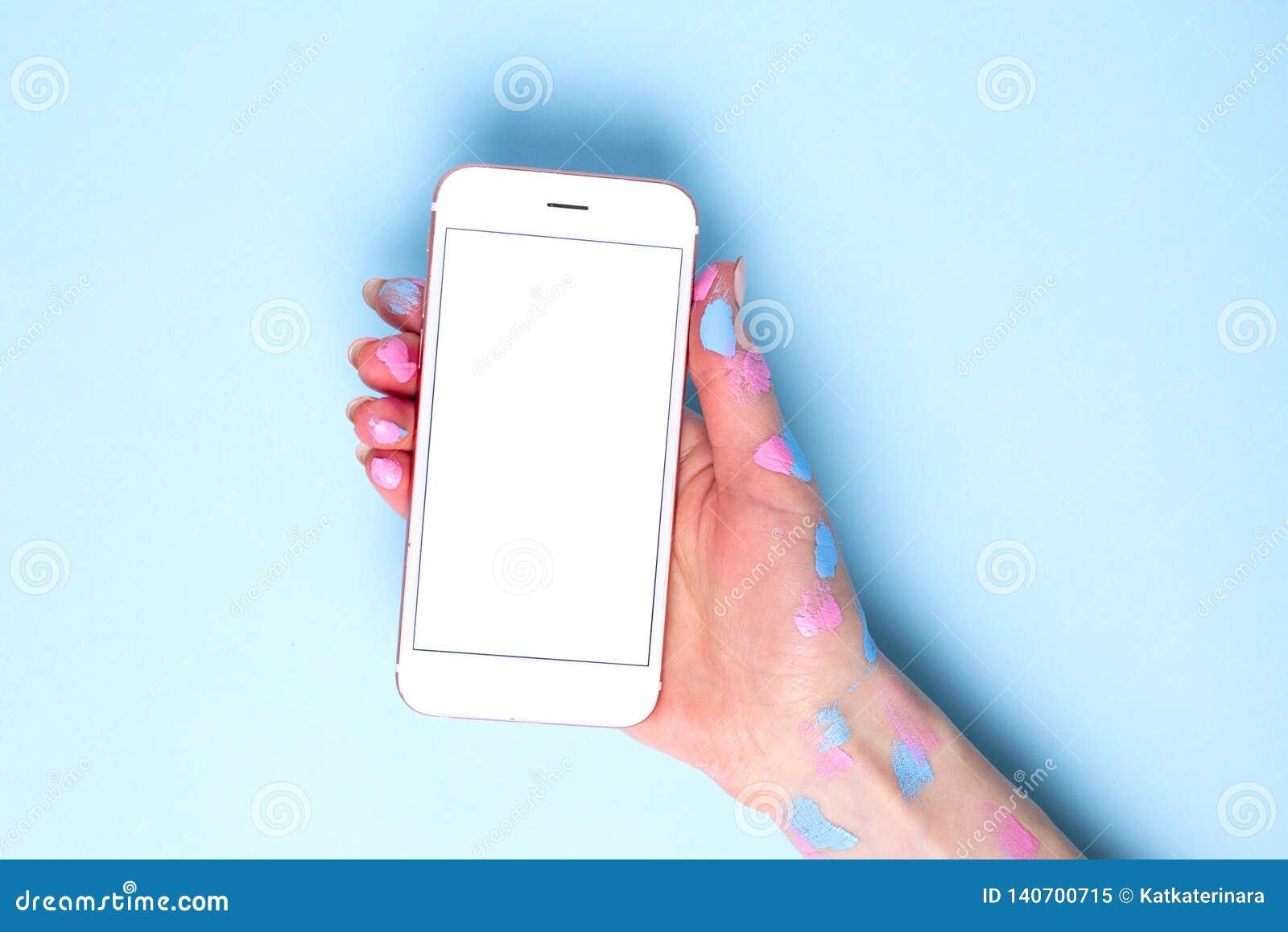 Telefone celular nas mãos das mulheres com a aquarela no fundo azul