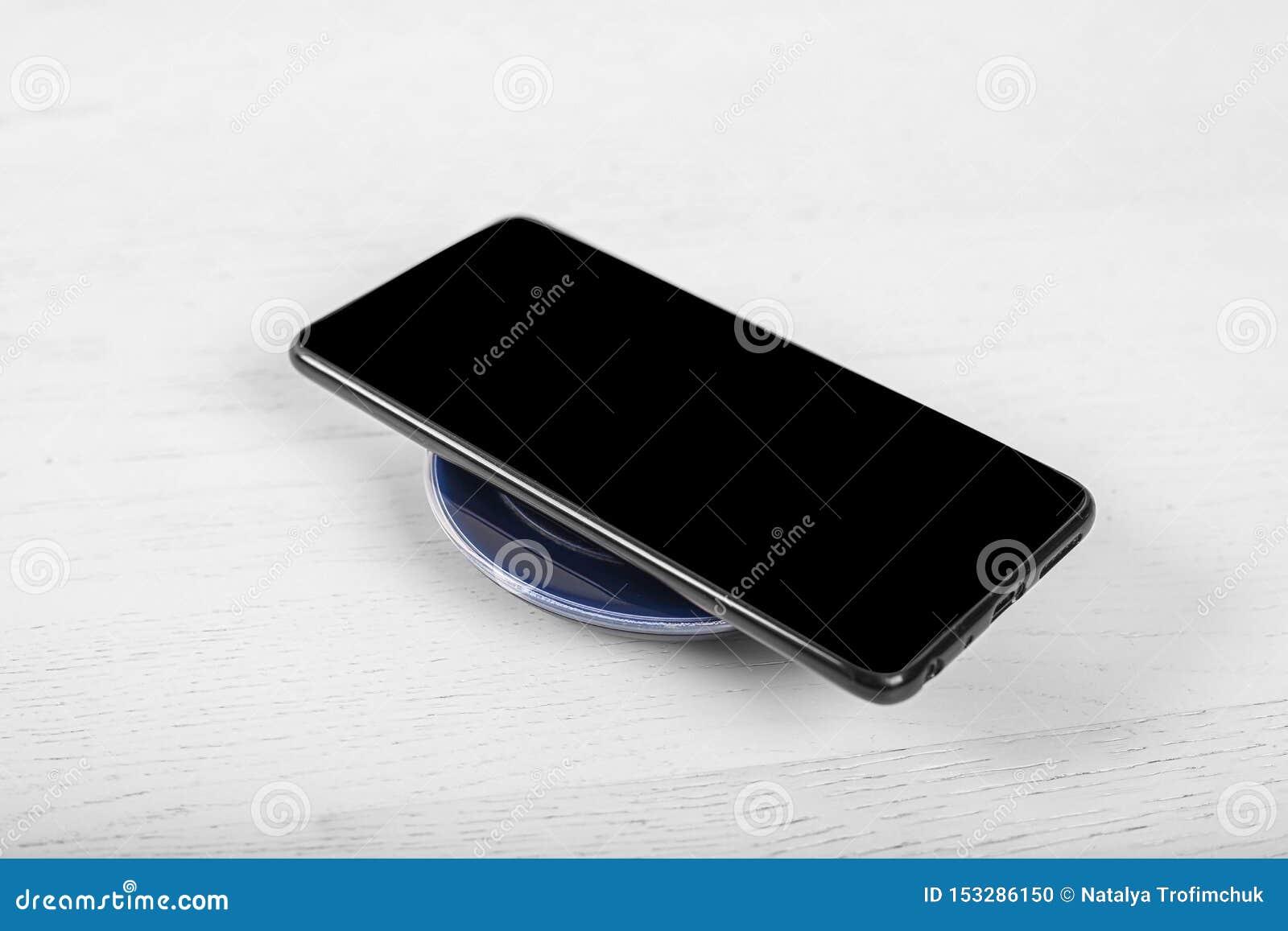 Telefone celular no carregador sem fio, equipamento moderno no fundo branco