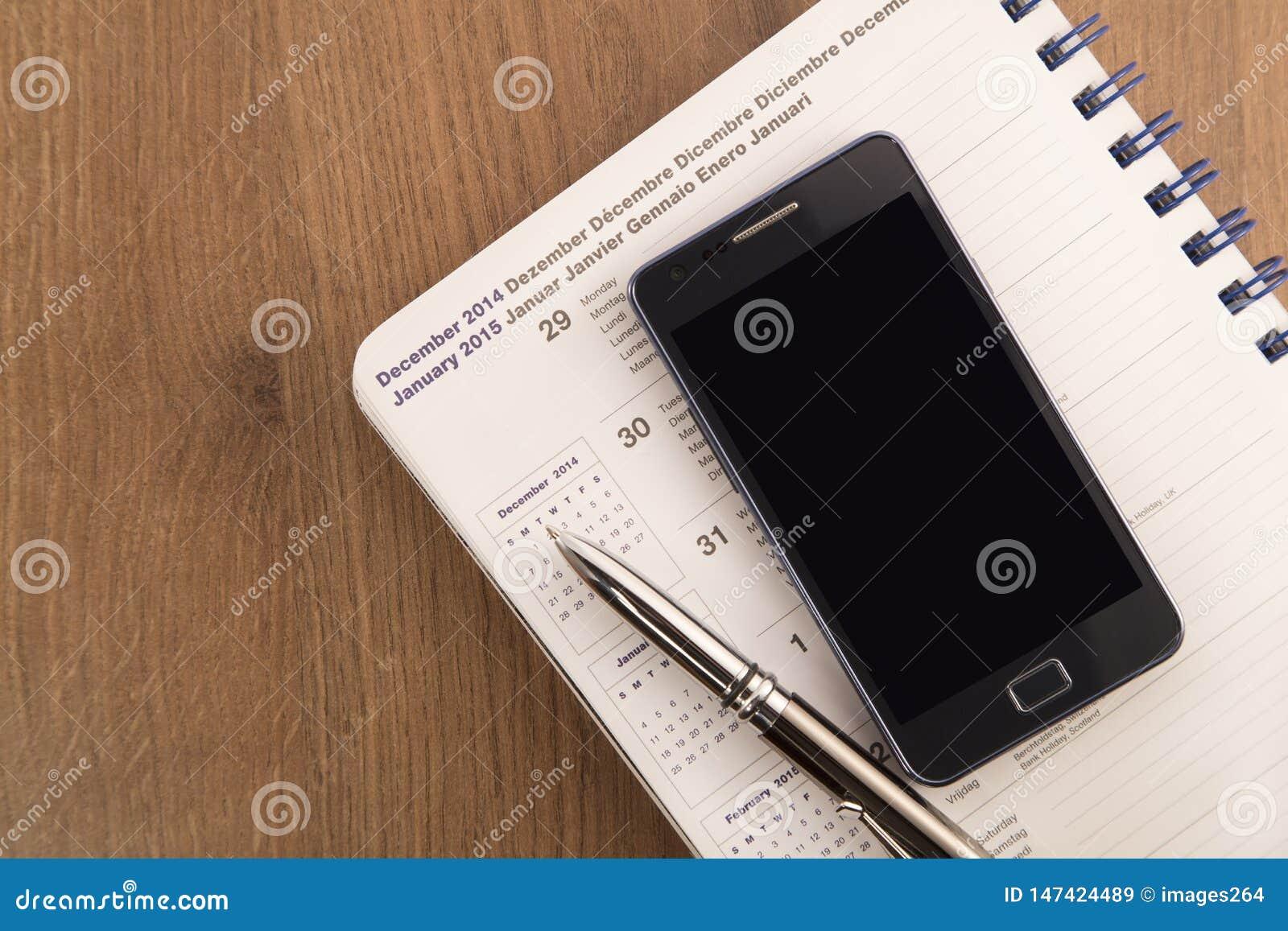 Telefone celular, pena e agenda