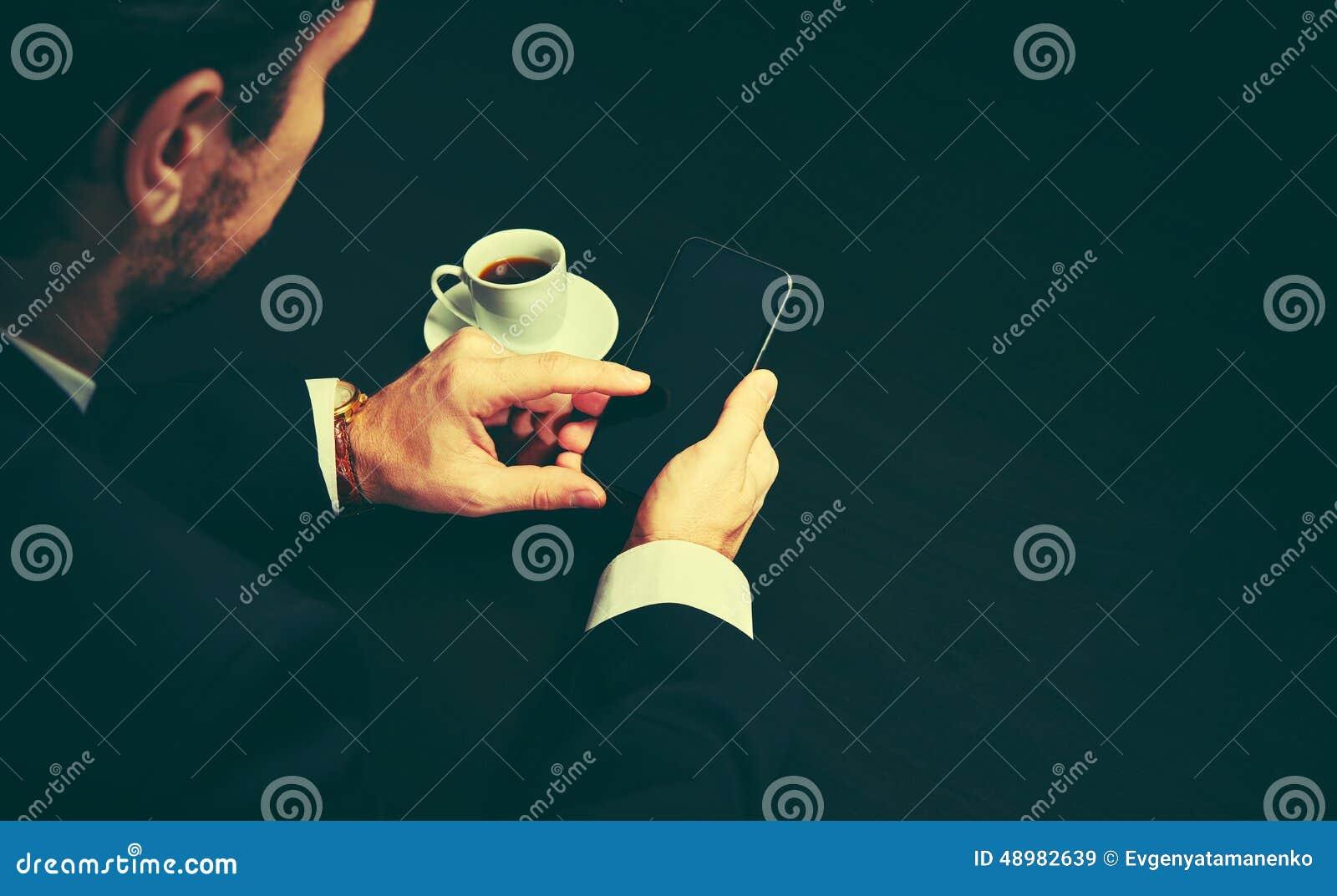 Telefone e uma xícara de café nas mãos de um homem de negócios em cores escuras