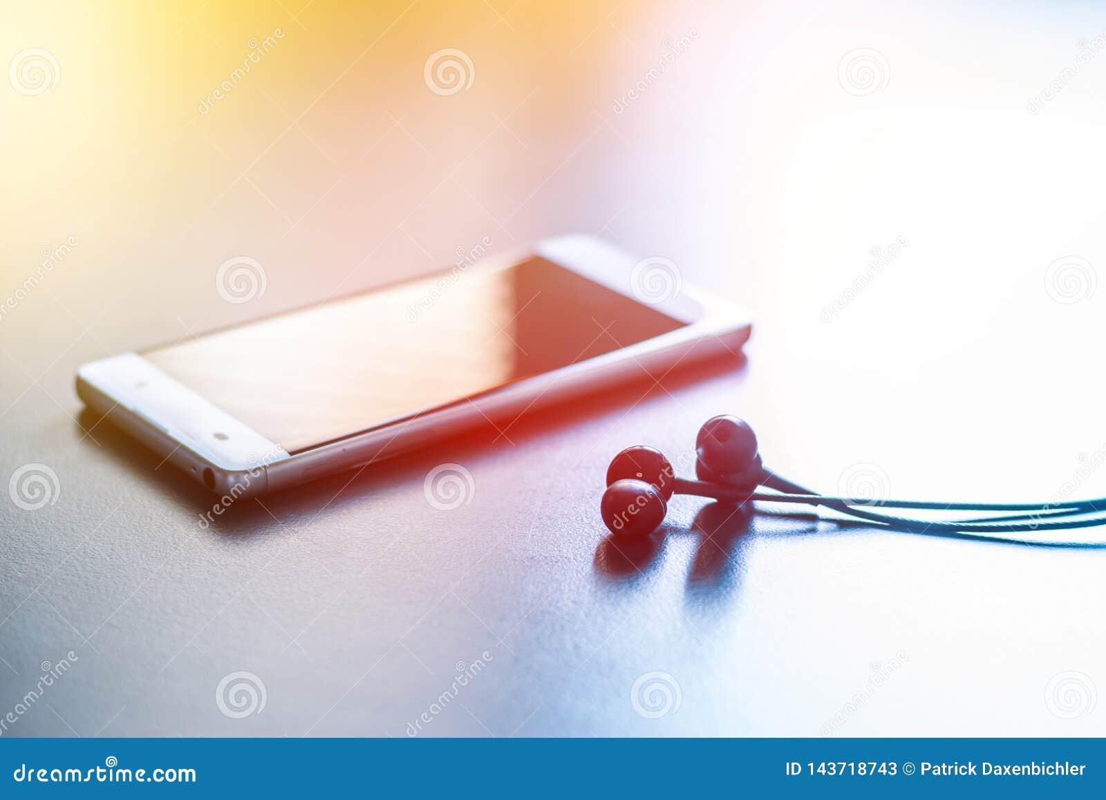Telefone esperto: O telefone e os fones de ouvido estão encontrando-se em uma tabela cinzenta, opinião de perspectiva