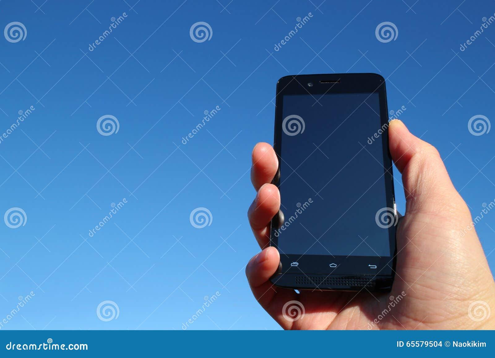 Telefone esperto preto e a mão no céu azul