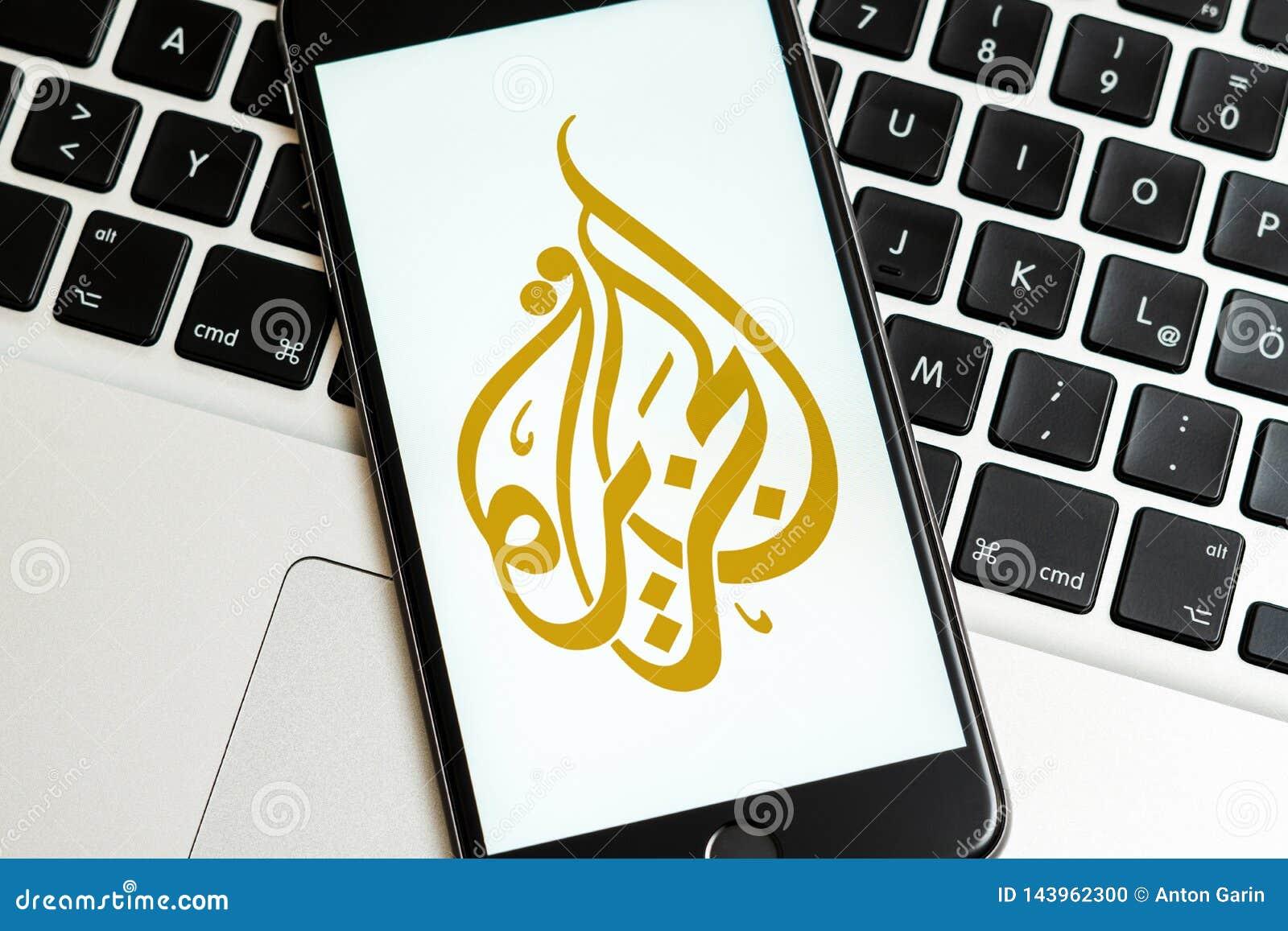 Telefone preto com logotipo dos meios noticiosos Al Jazeera na tela