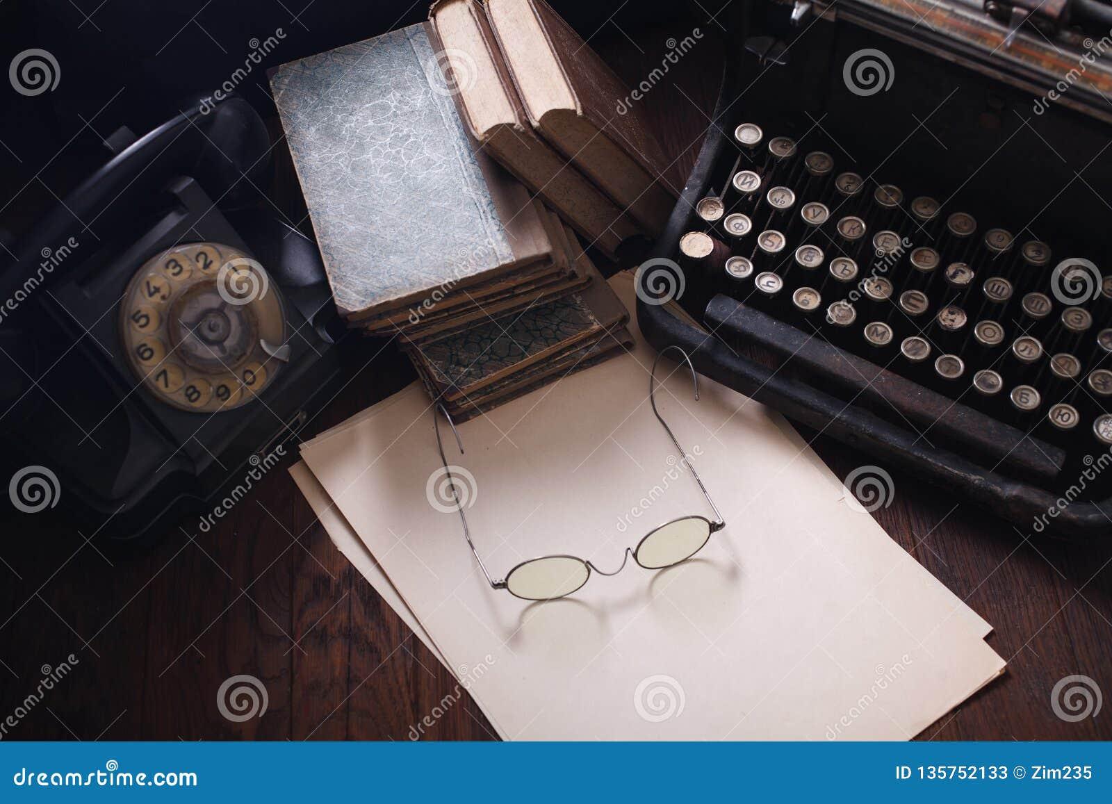 Telefone retro velho com máquina de escrever do vintage e uma folha de papel vazia na placa de madeira
