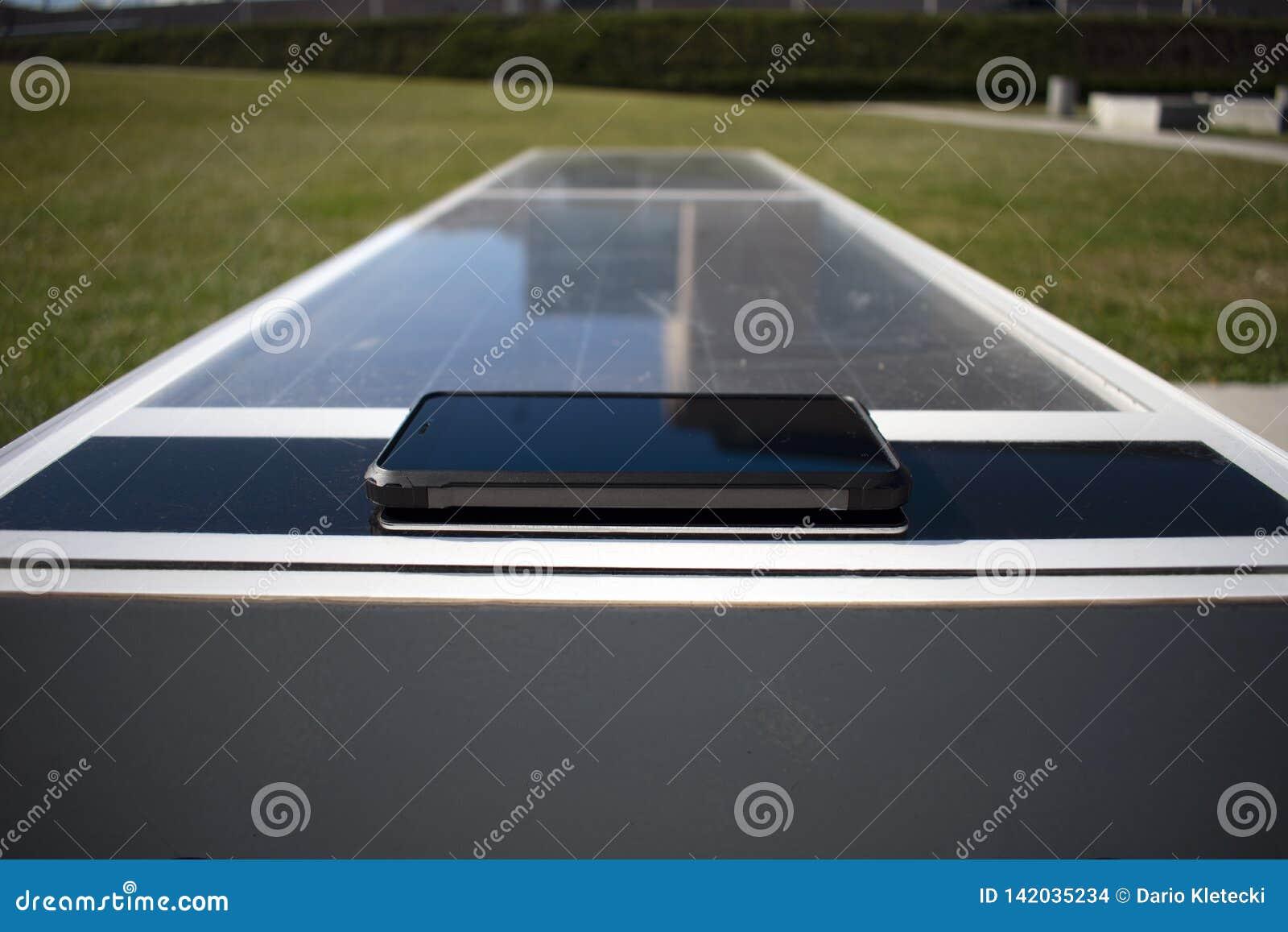 Telefono cellulare che fa pagare a distanza su un banco solare