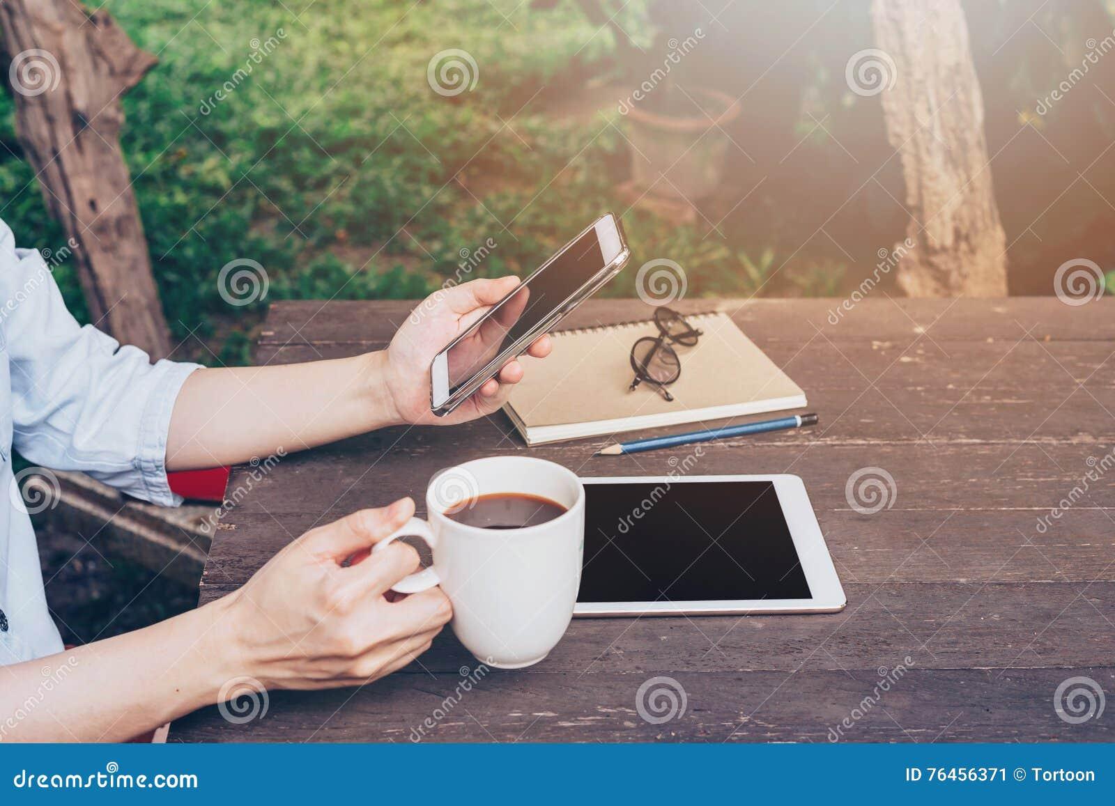 Telefono della tenuta della mano della donna e telefono usando sulla tavola in giardino