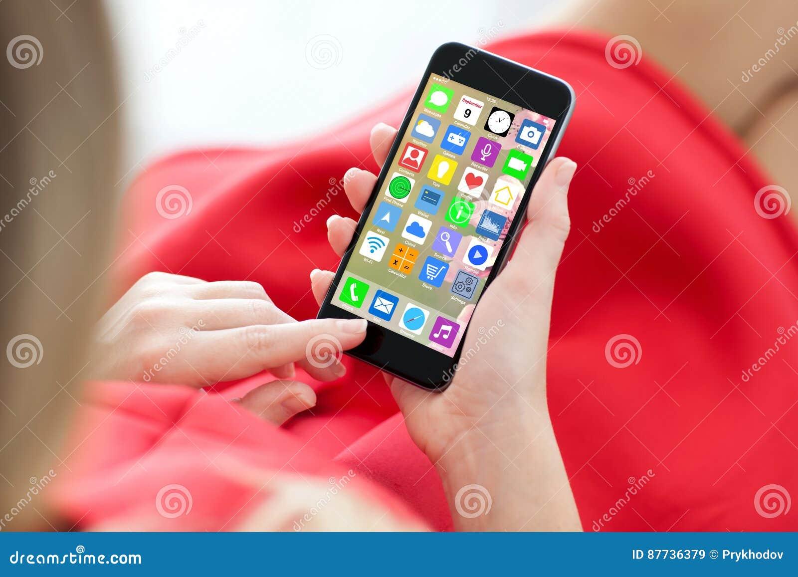 Telefono rosso della tenuta del vestito dalla donna con i apps delle icone dello schermo domestico