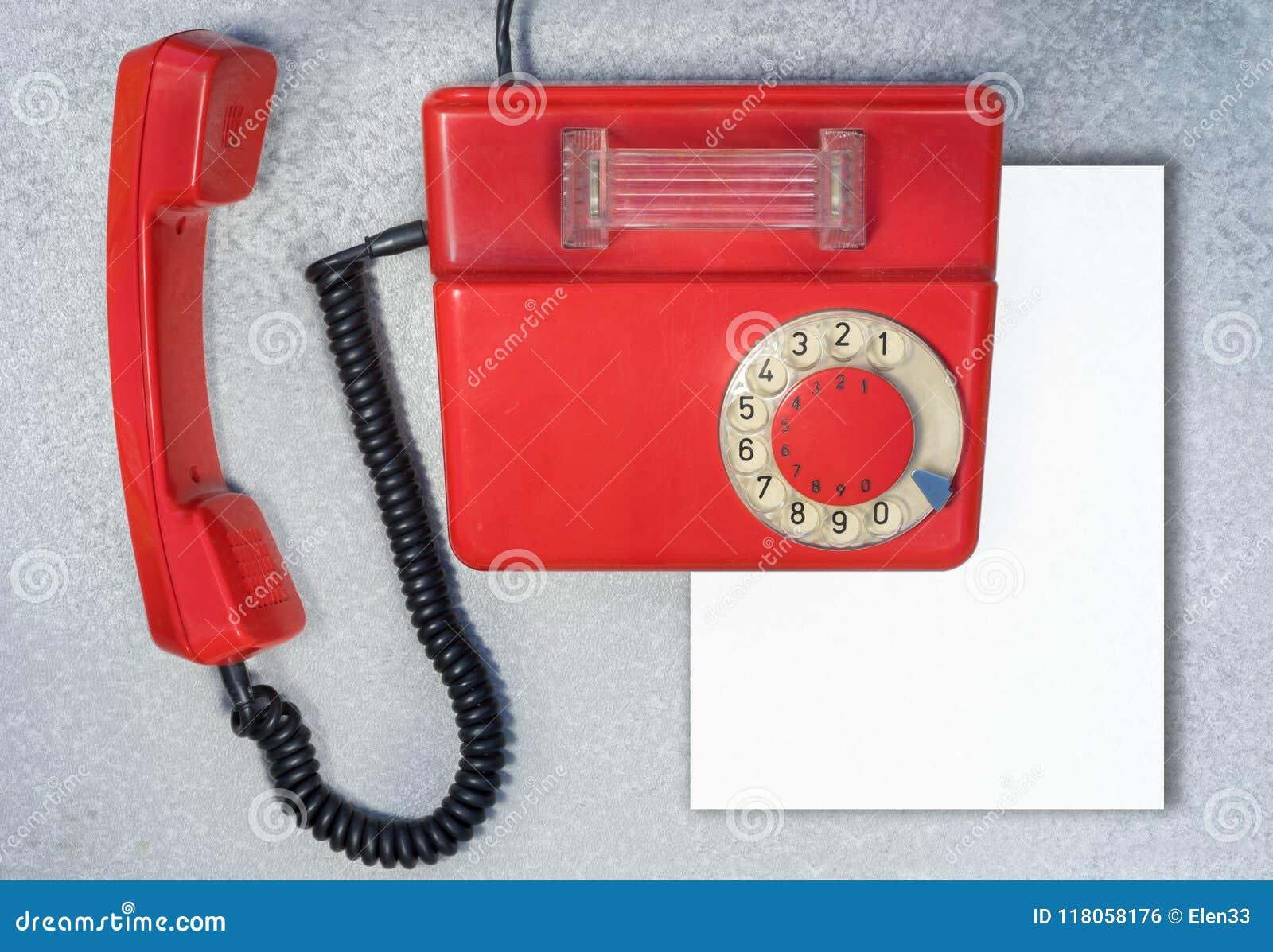 Telefono rotatorio antico rosso con il foglio bianco di carta