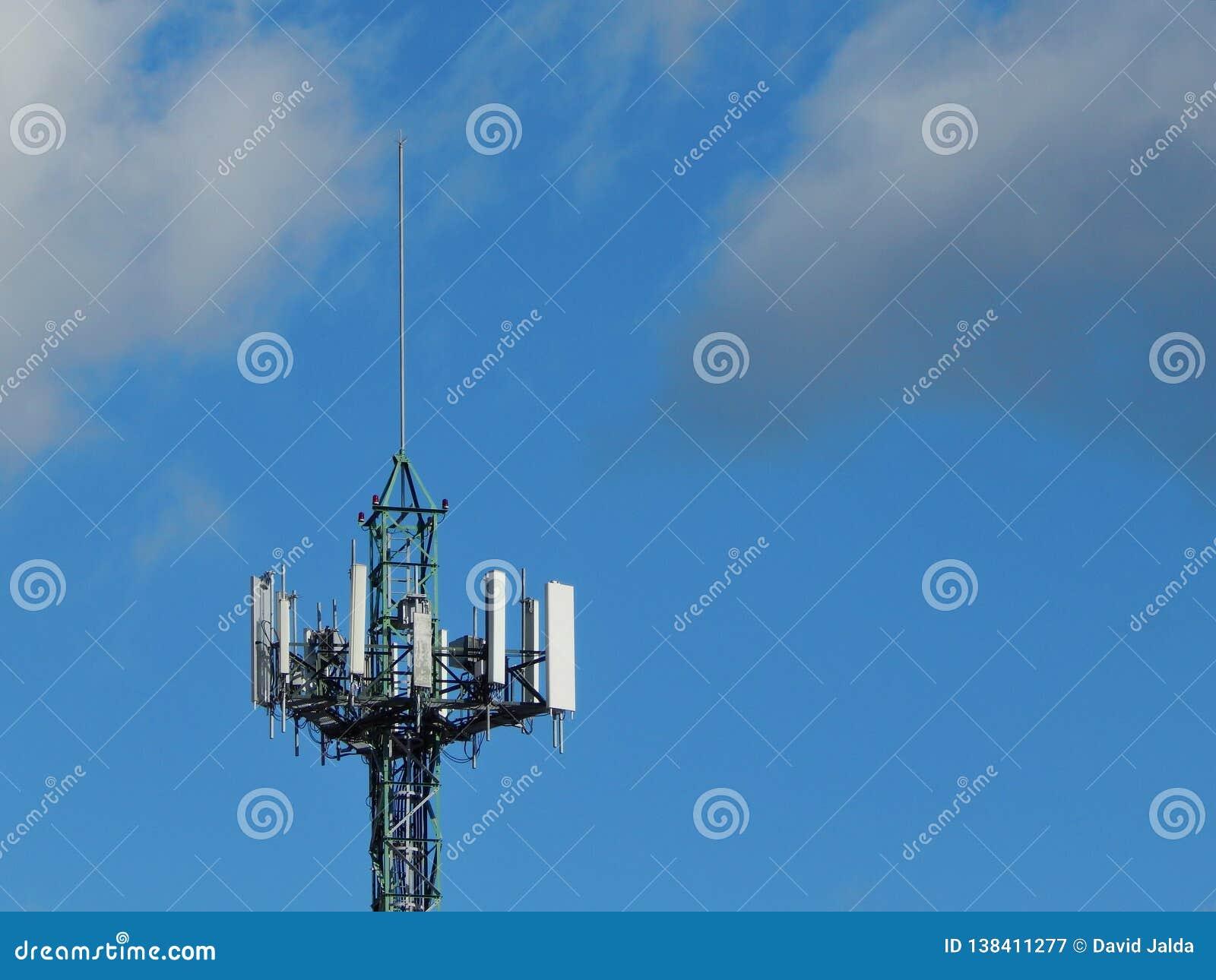 Telekommunikationantenn och blå himmel med moln
