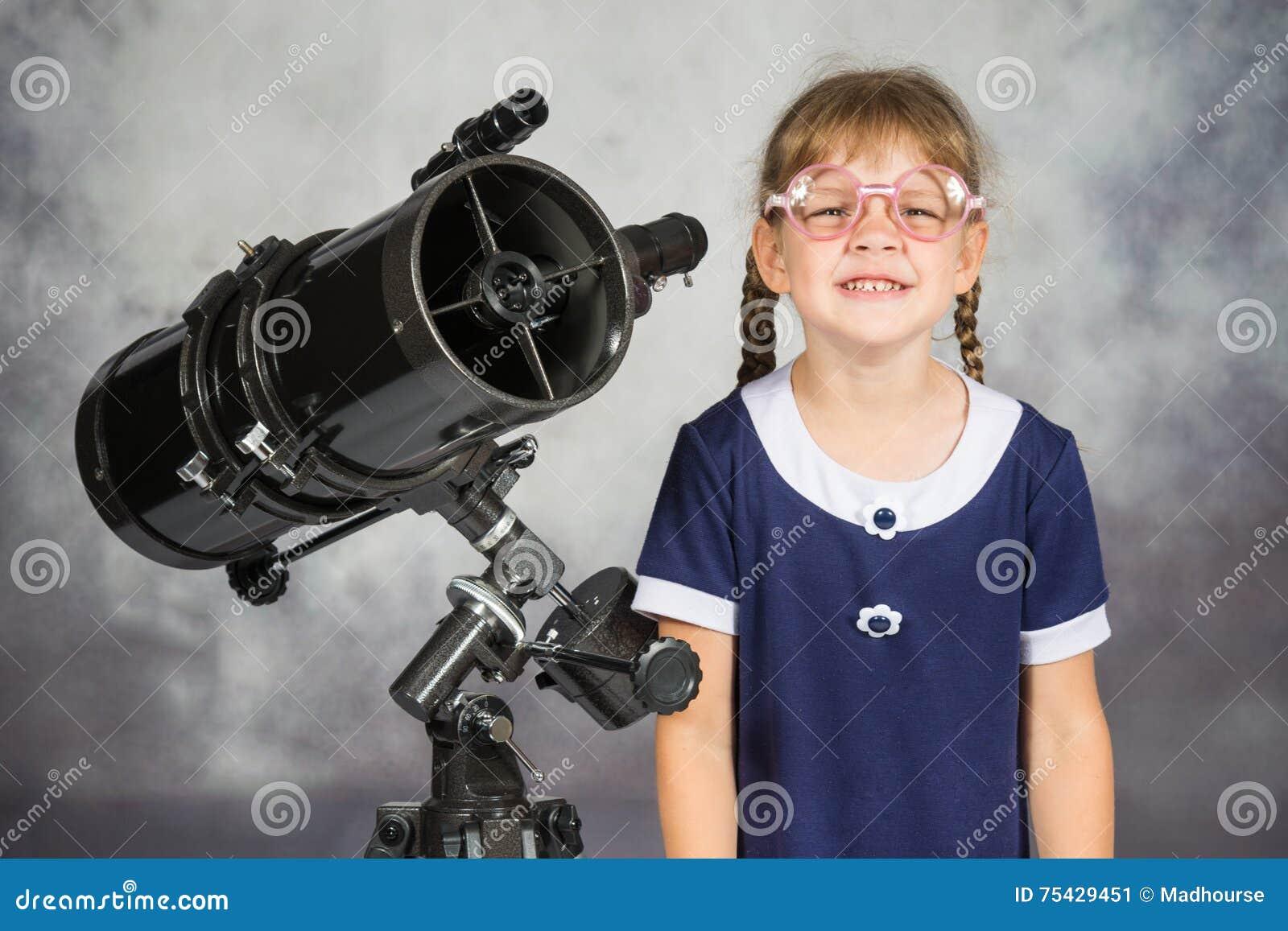 Telescopio que hace una pausa sonriente divertido del astrónomo aficionado con gafas de la muchacha