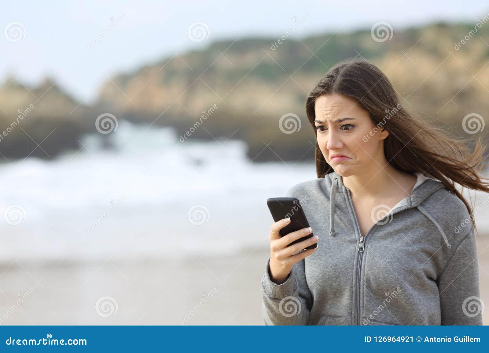 Teleurgesteld de telefoonbericht van de tienerlezing op het strand