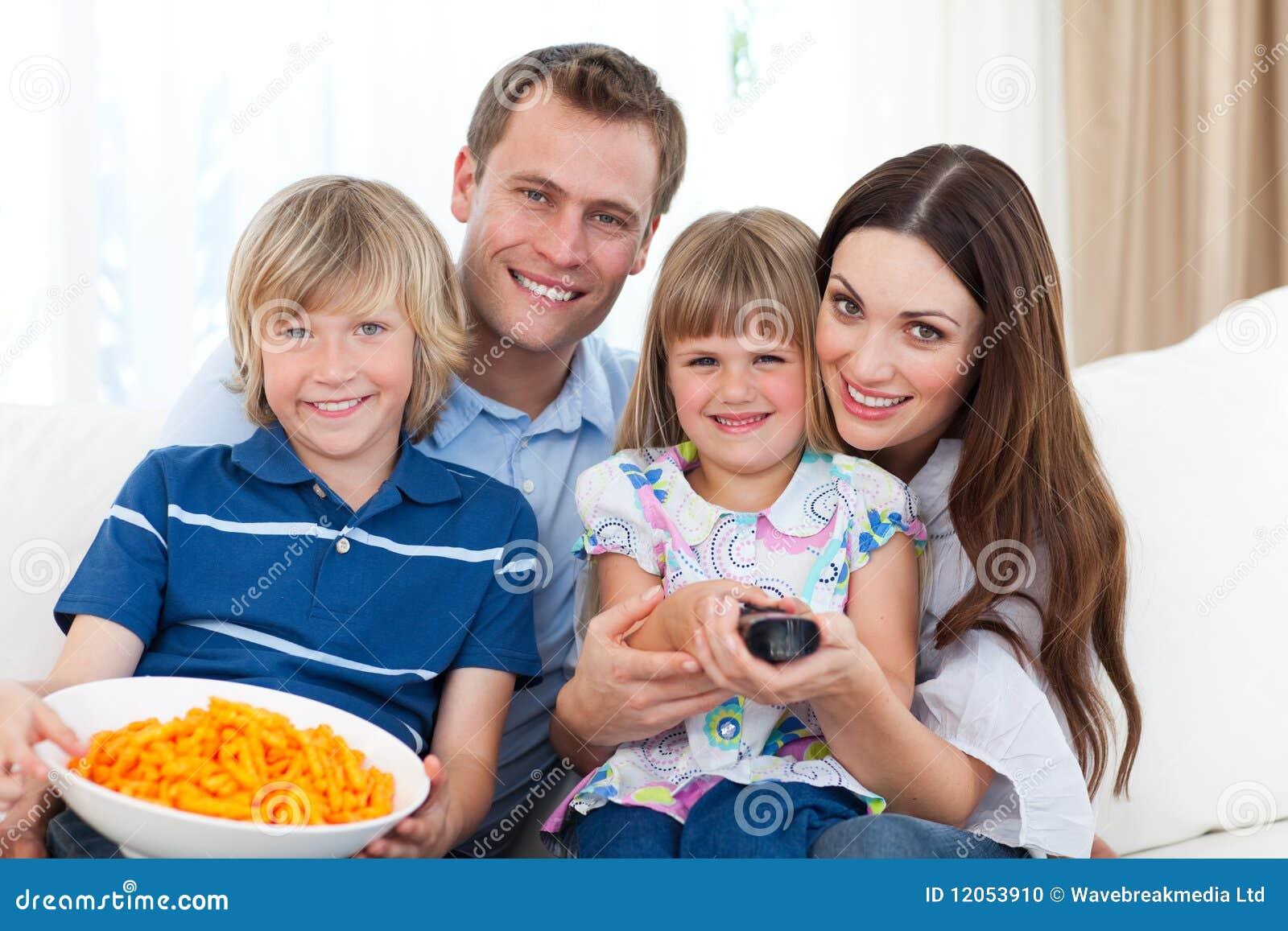 Televisión de la familia feliz y virutas de observación de la consumición