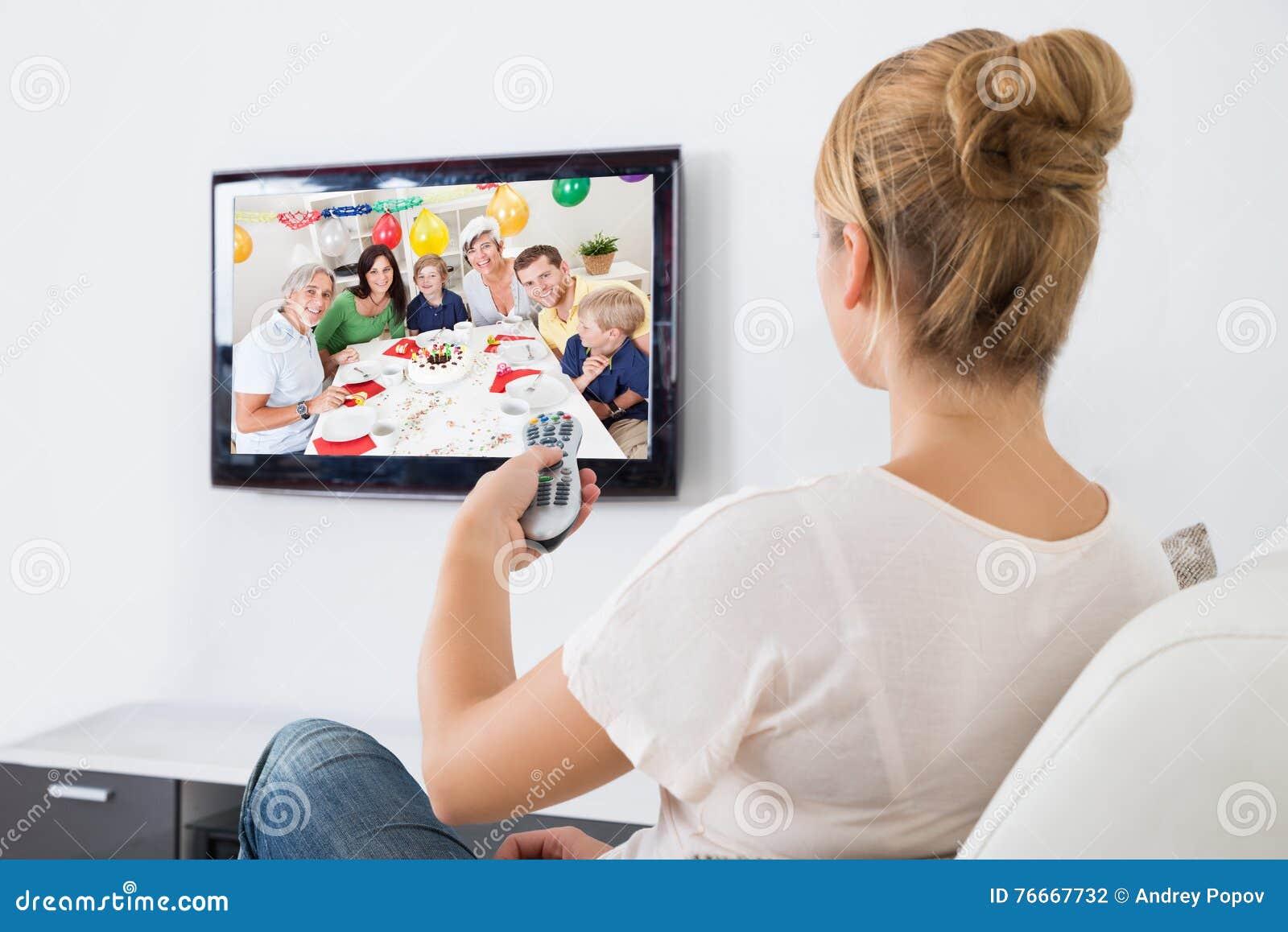 Televisión de observación de la mujer joven mientras que se sienta en el sofá