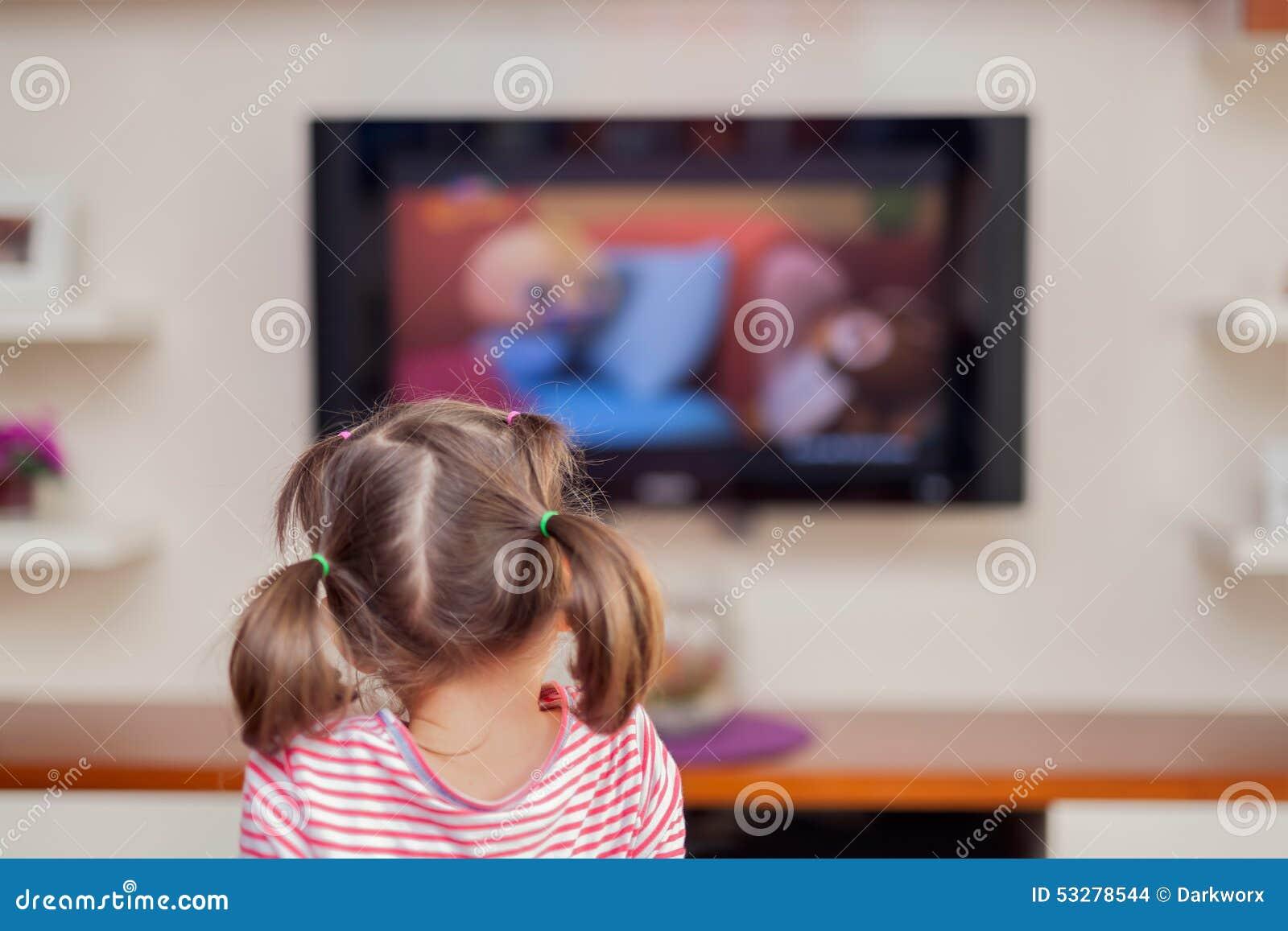 Televisión de observación de la pequeña muchacha linda con la atención