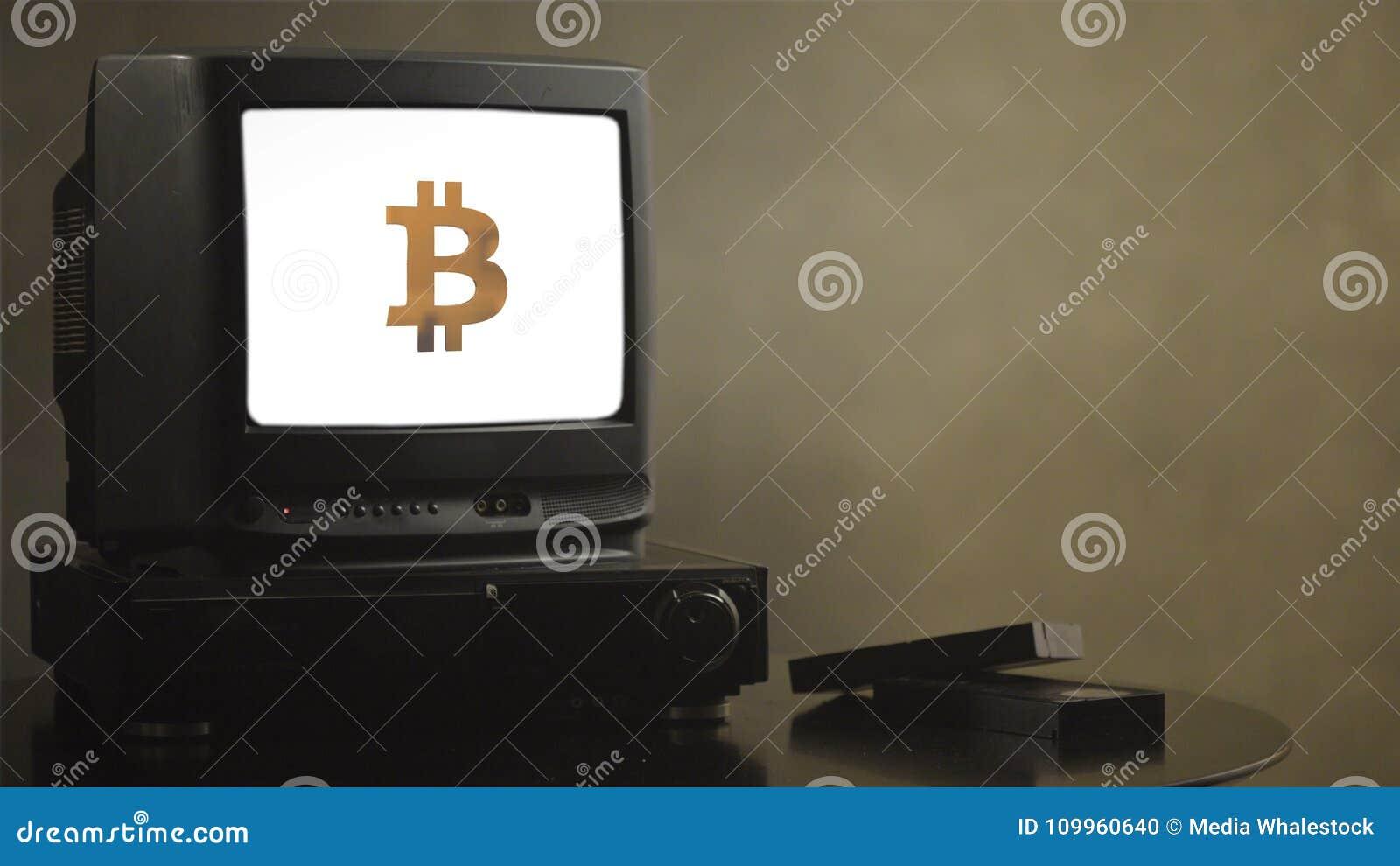 Televisión del vintage en la tabla de madera con el bitcoin TV vieja que muestra el bitcoin Cerca de la TV hay casetes y vídeo de