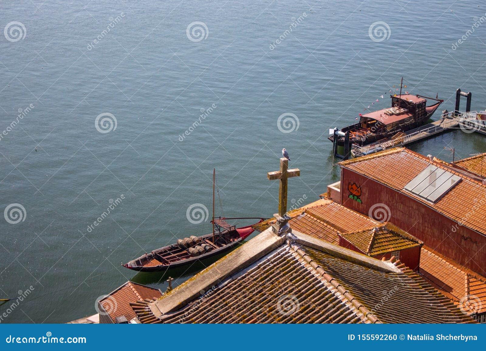 Telhados vermelhos com cruz na opinião superior do fundo de Douro do rio Terraplenagem com telhado da igreja e cruz de madeira em