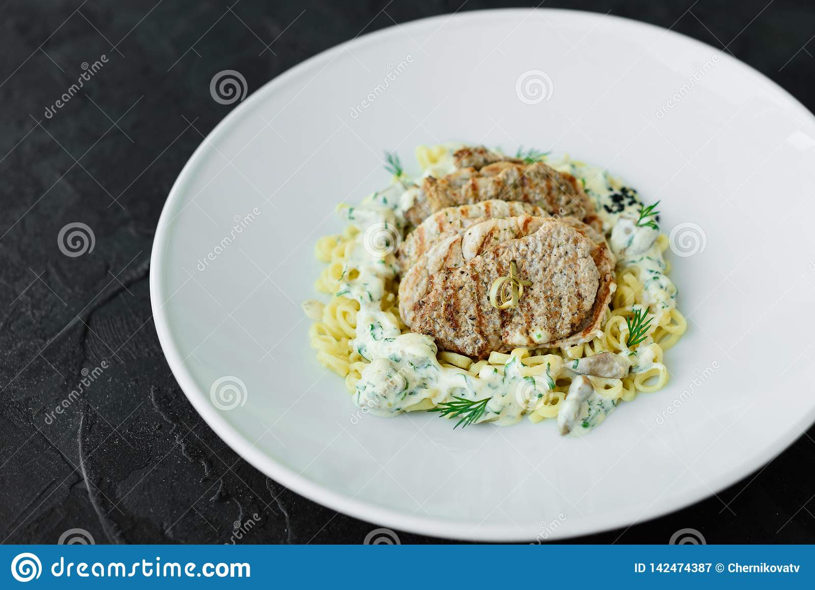 Teller mit Fleischstücken, -teigwaren, -GRÜNS und -soße von Fettleber