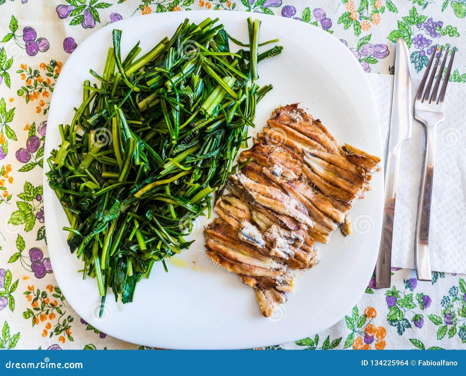 Teller von gebackenen Sardellen mit Zichorie