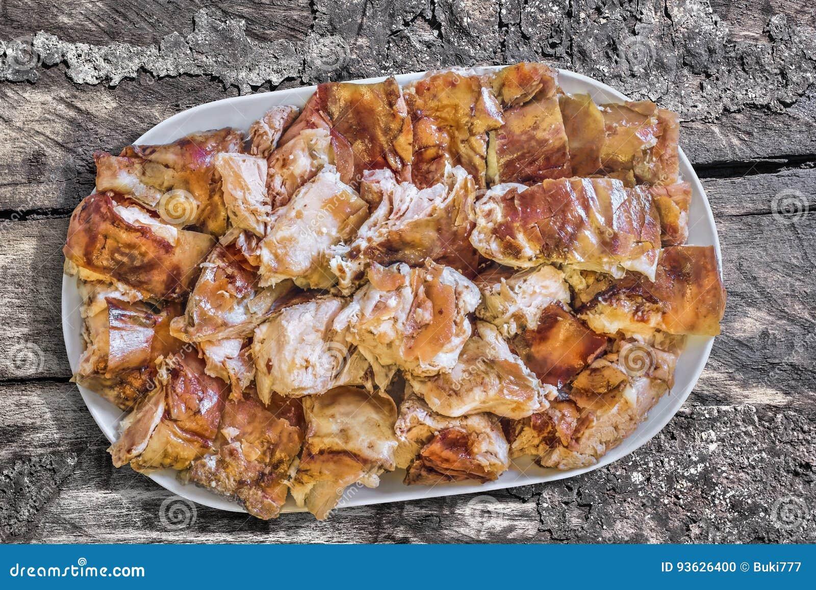 Tellervoll des Spucken gebratenen Schweinefleisch-Satzes auf alter verwitterter gebrochener grober Kiefernholz-Schmutz-Tischplatt