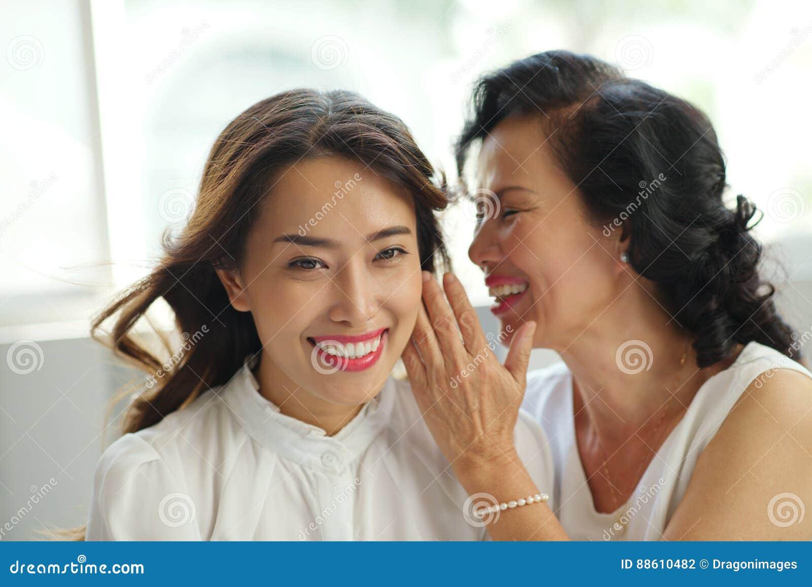Mature Asian women telling secret to her daughter