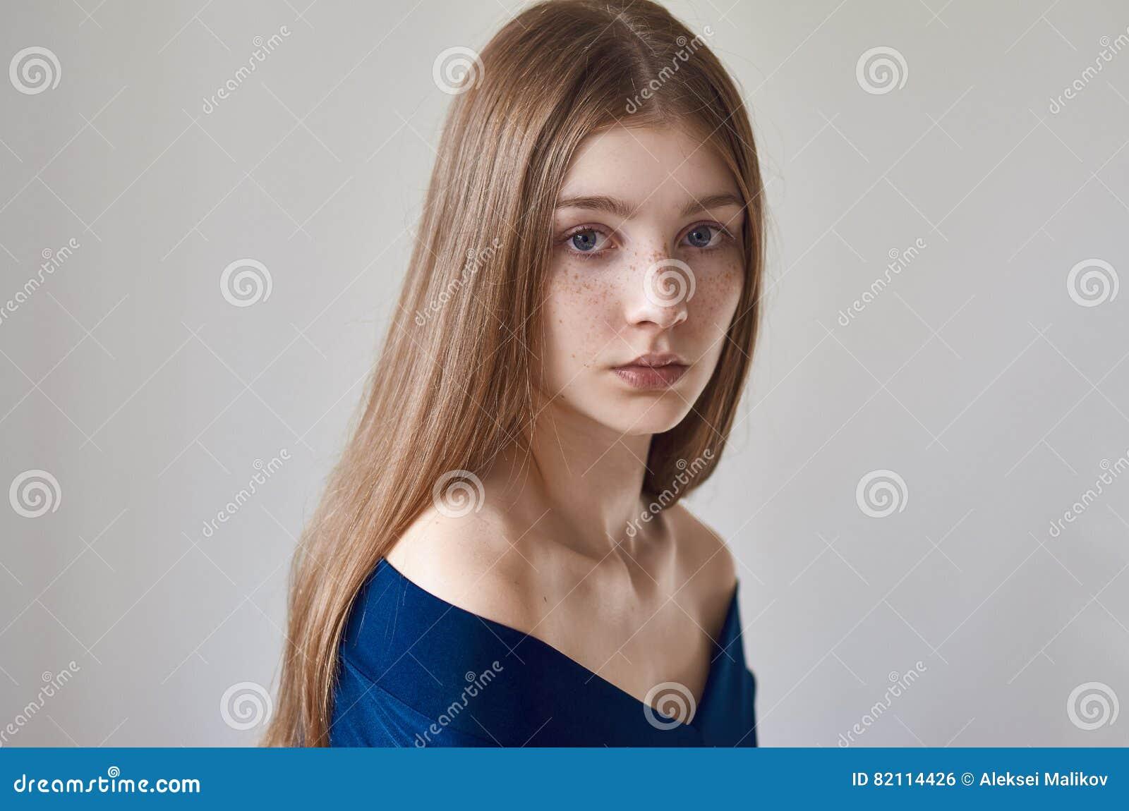 Tema da beleza: retrato de uma moça bonita com as sardas em sua cara e em vestir um vestido azul em um fundo branco no studi
