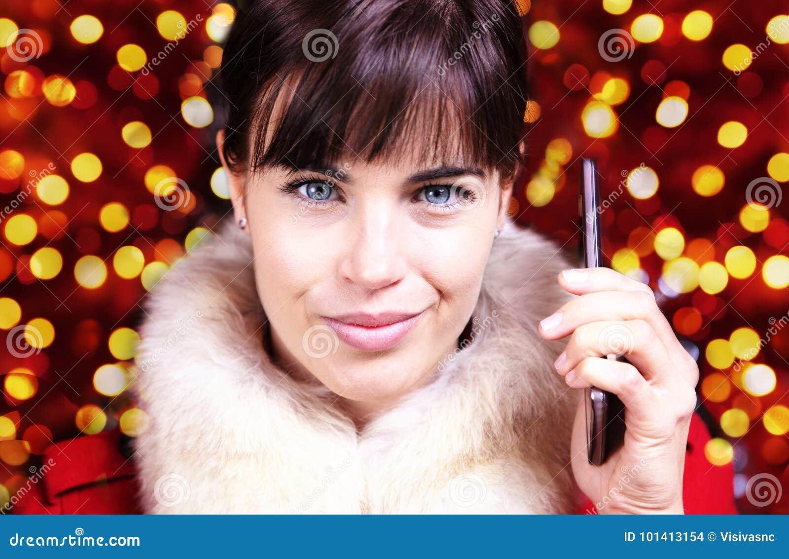Tema de la Navidad, mujer sonriente que usa smartphone en brigh borroso